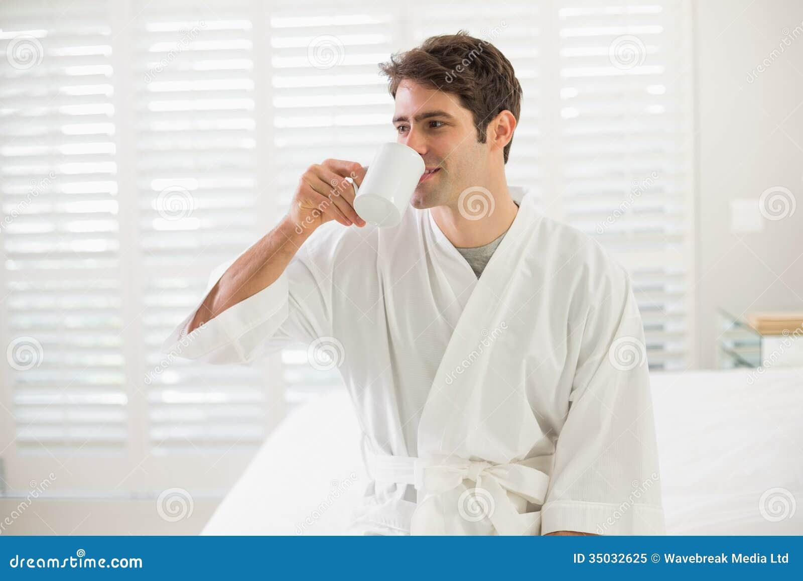 Jeune homme en caf potable de peignoir dans la chambre for Chambre a coucher homme