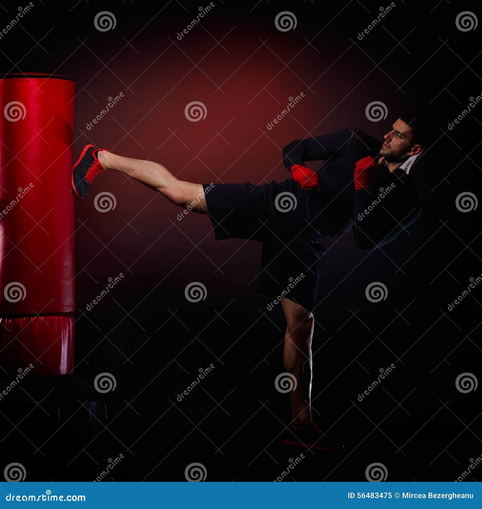 Jeune homme exerçant la boxe de sac
