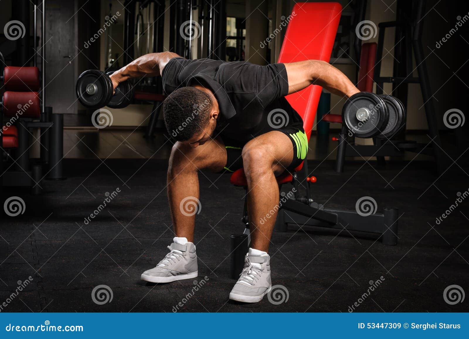 Jeune homme faisant Bent Over Dumbbell Reverse assis