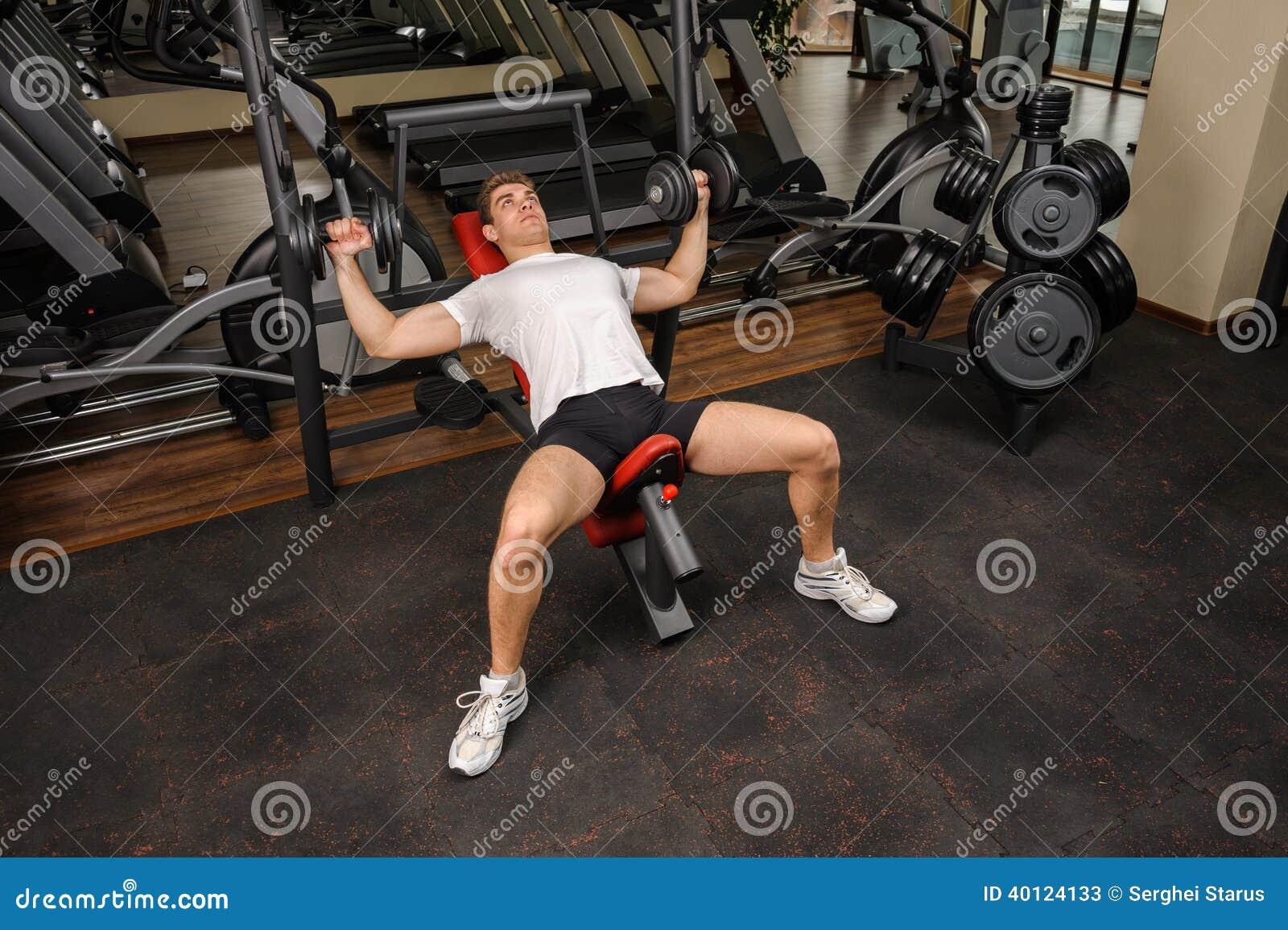 Jeune homme faisant la séance d entraînement de banc à presse de pente d haltère dans le gymnase