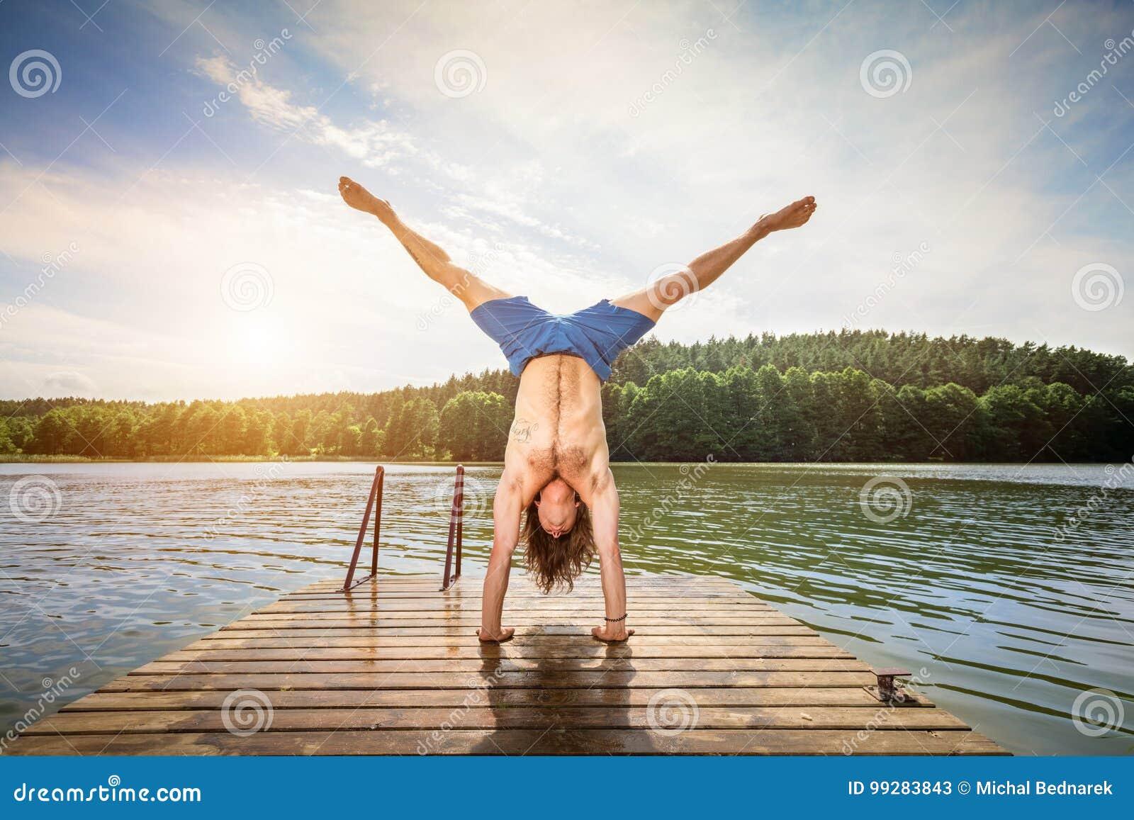 Jeune homme faisant un appui renversé sur une jetée en bois