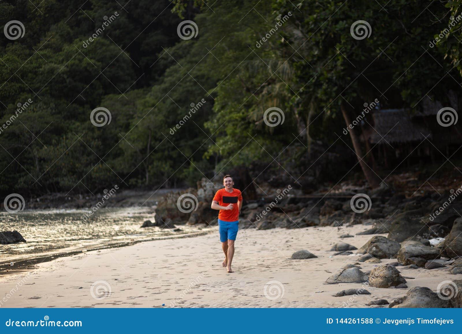 Jeune homme heureux courant sur une plage sur Ko Chang, la meilleure destination de voyage de la Thaïlande en avril 2018 - pour l