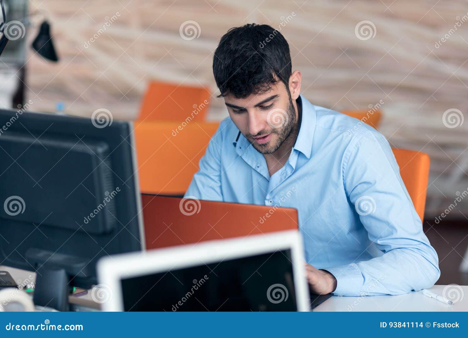 Jeune homme heureux daffaires travaillant sur lordinateur de