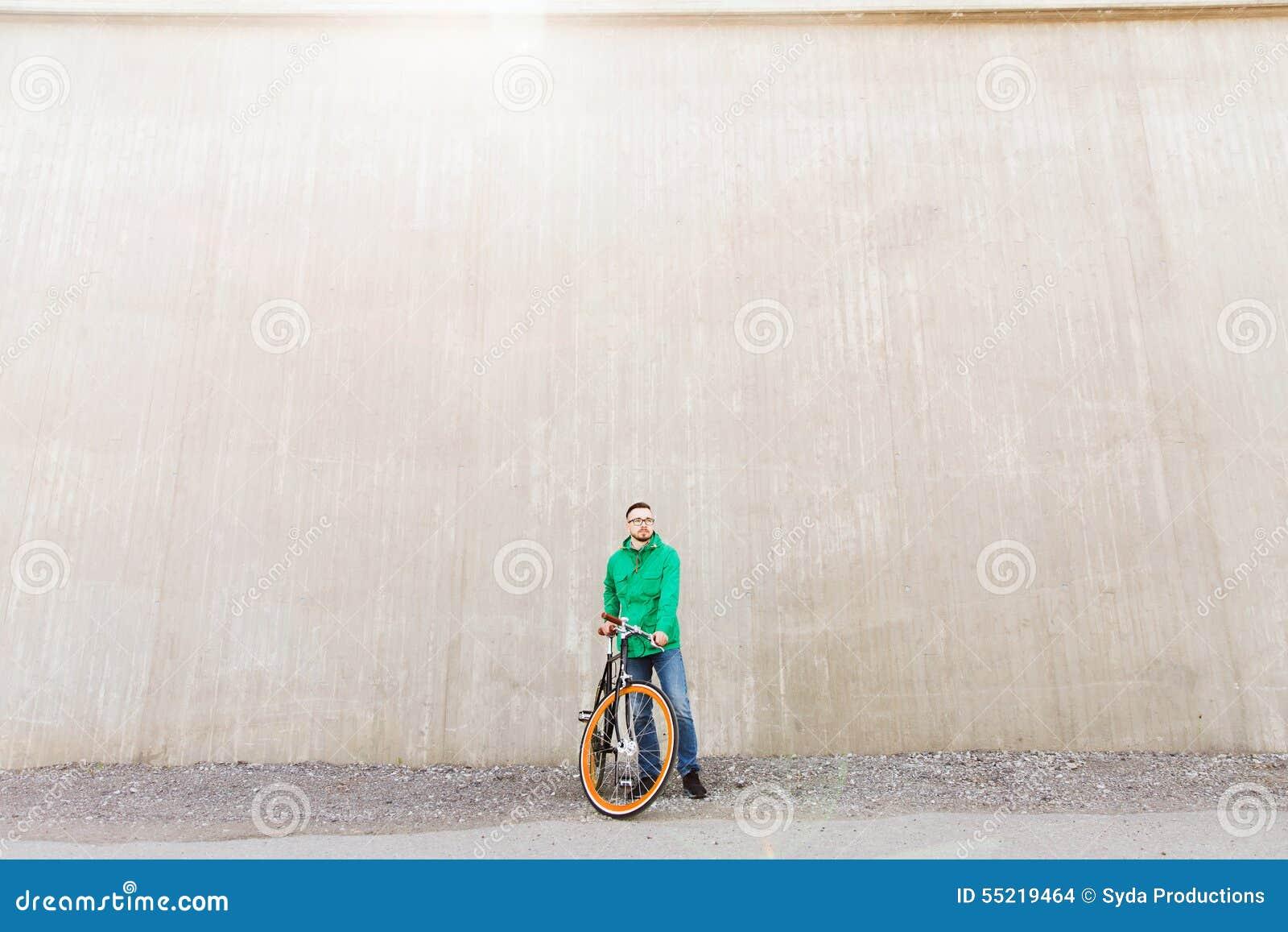 Jeune homme heureux de hippie avec le vélo fixe de vitesse