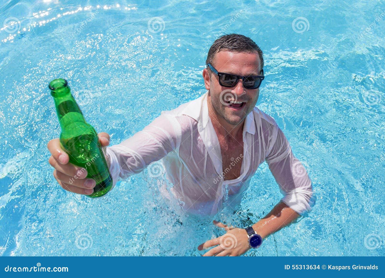 Jeune homme heureux faisant la fête dans la piscine