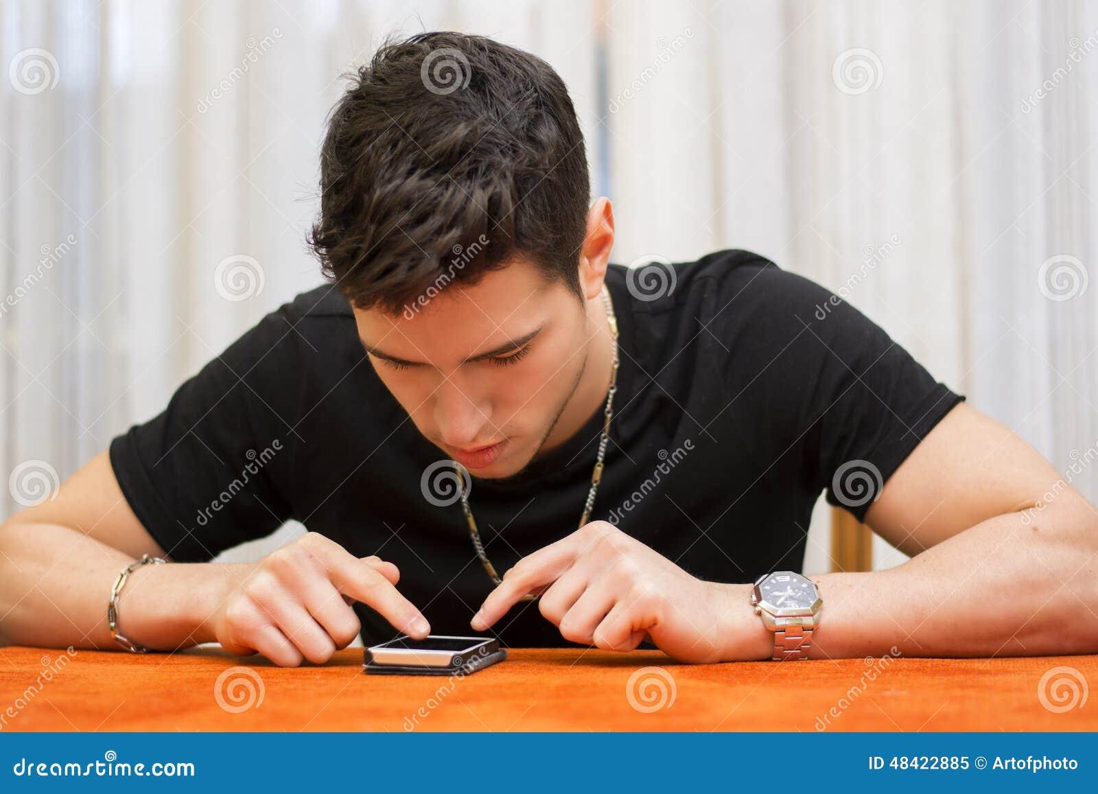 Jeune homme introduisant un message textuel à son téléphone