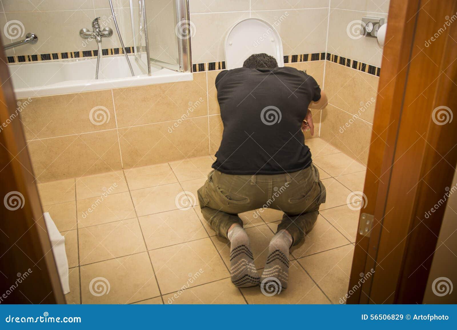 Jeune homme ivre vomissant dans la toilette à la maison