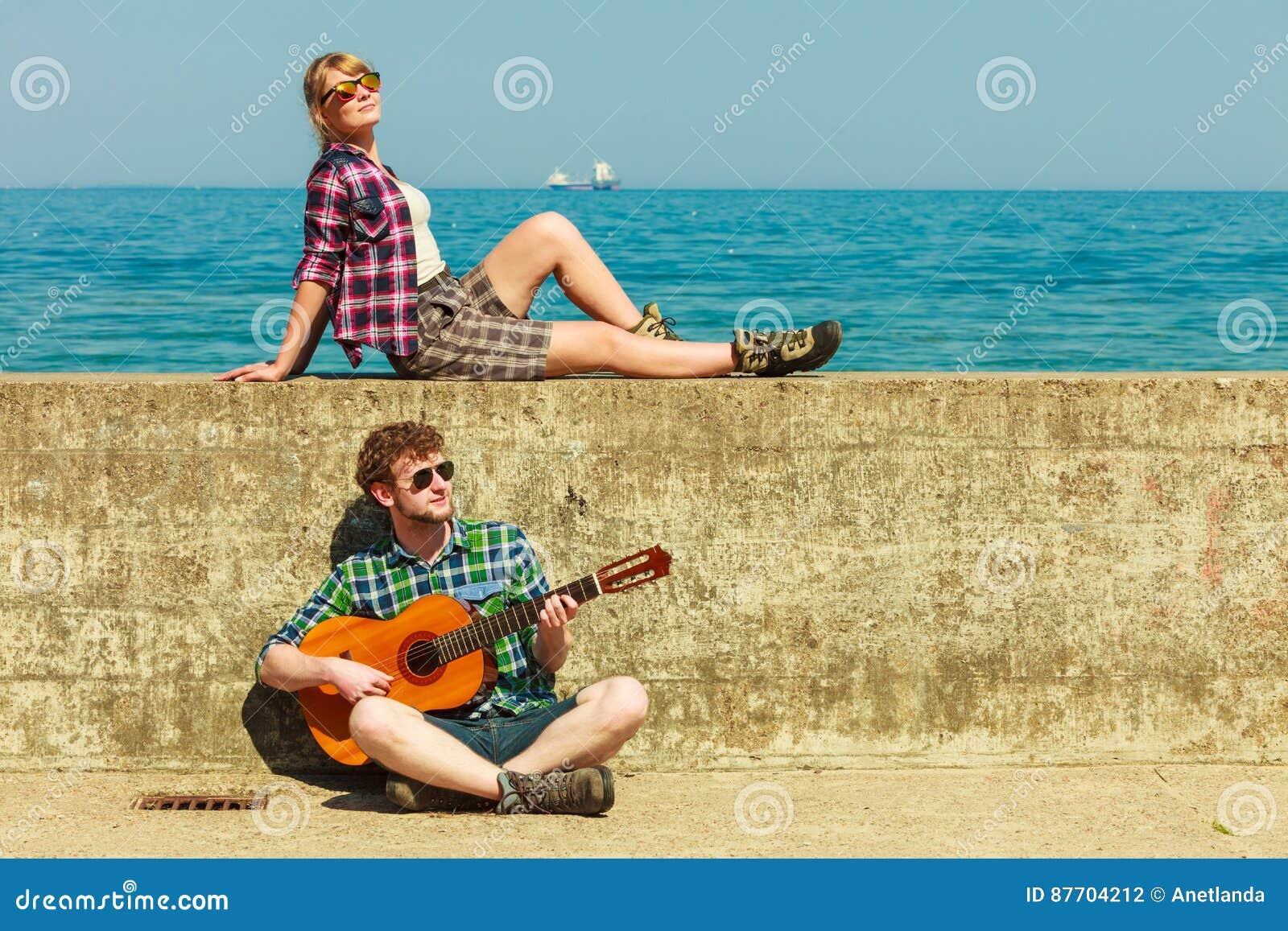 Jeune homme jouant la guitare à son amie par le bord de la mer