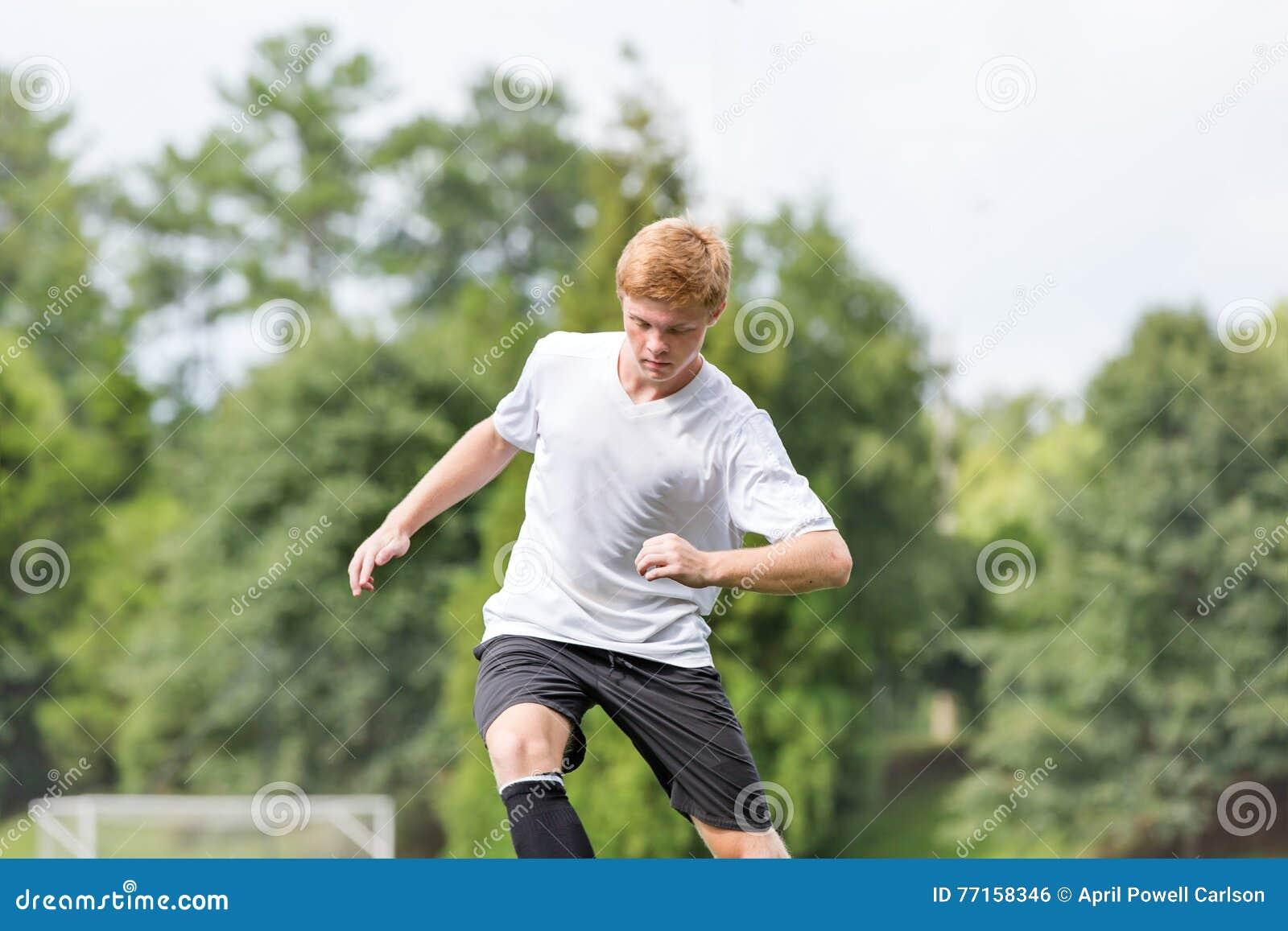 Jeune homme jouant le football - faire un mouvement du football