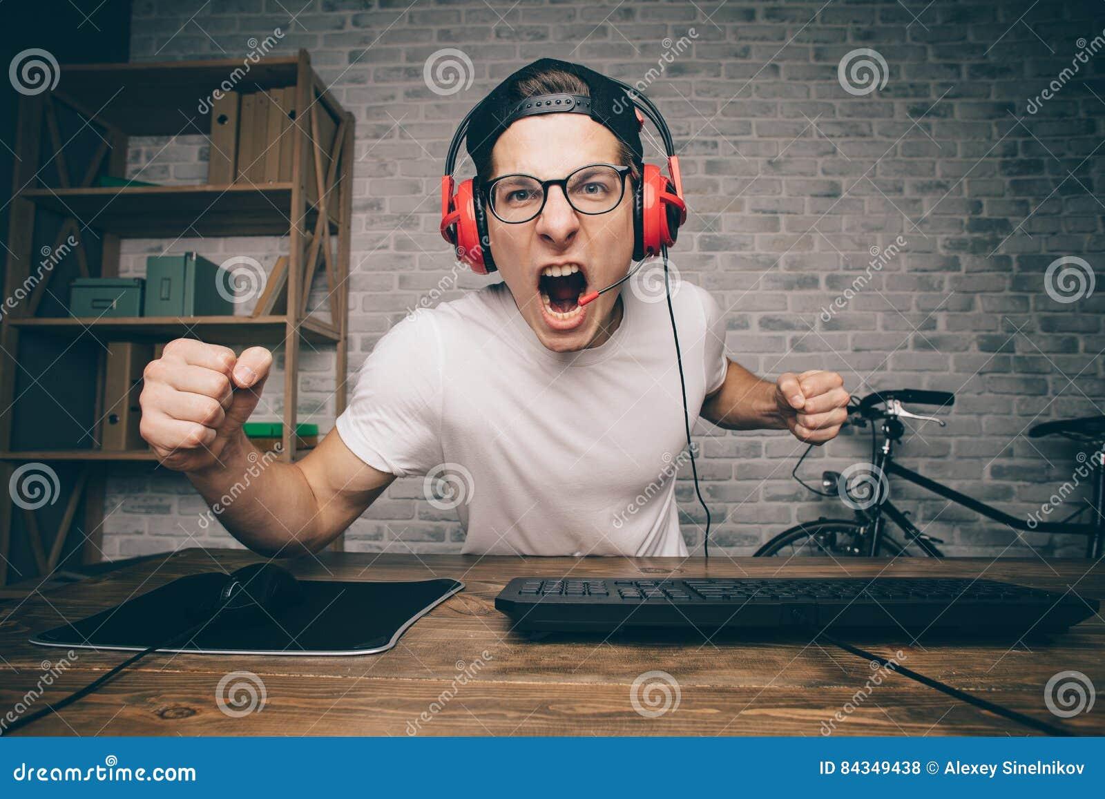 Jeune homme jouant le jeu à la maison et coulant la vidéo de playthrough ou de revue du projet