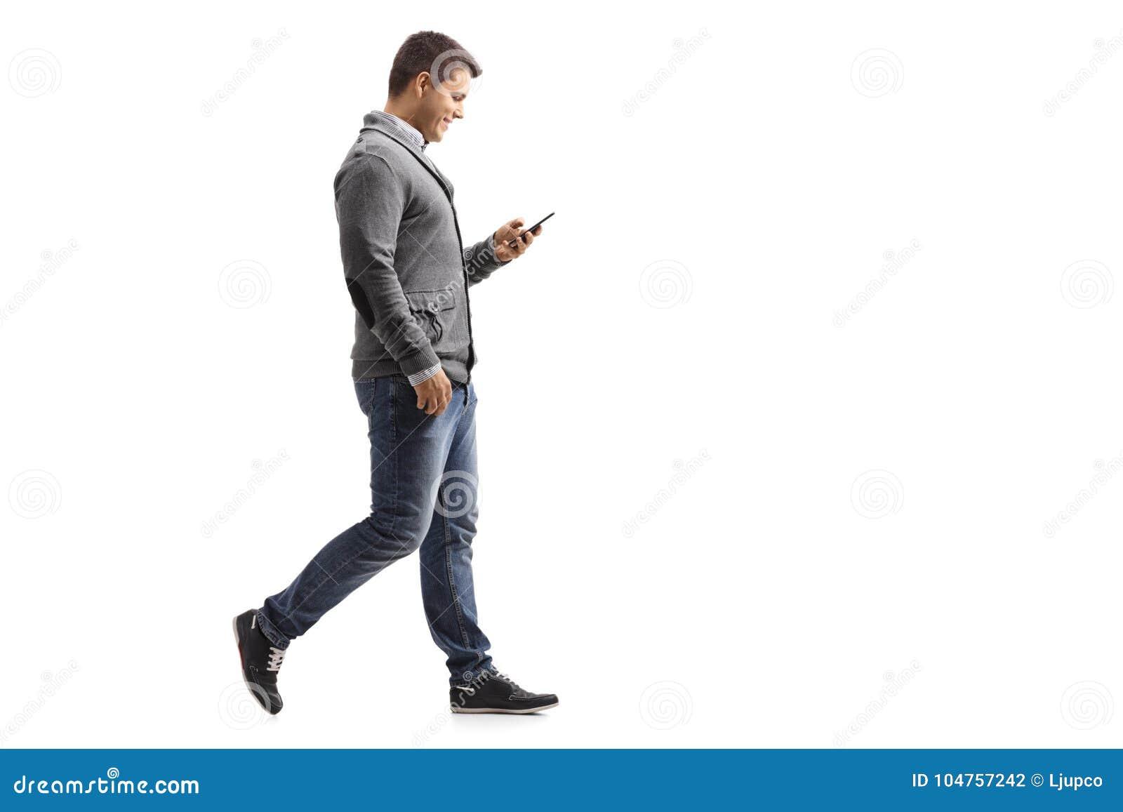 Jeune Homme Marchant Et à L'aide D'un Téléphone Photo ...