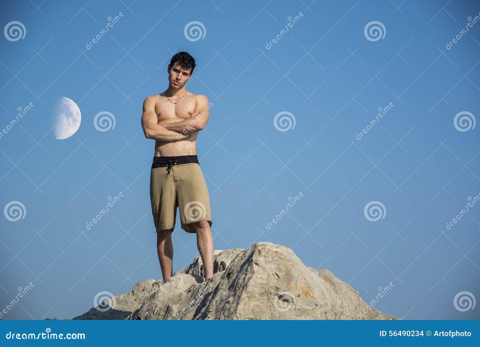 Jeune homme musculaire sans chemise contre le ciel avec