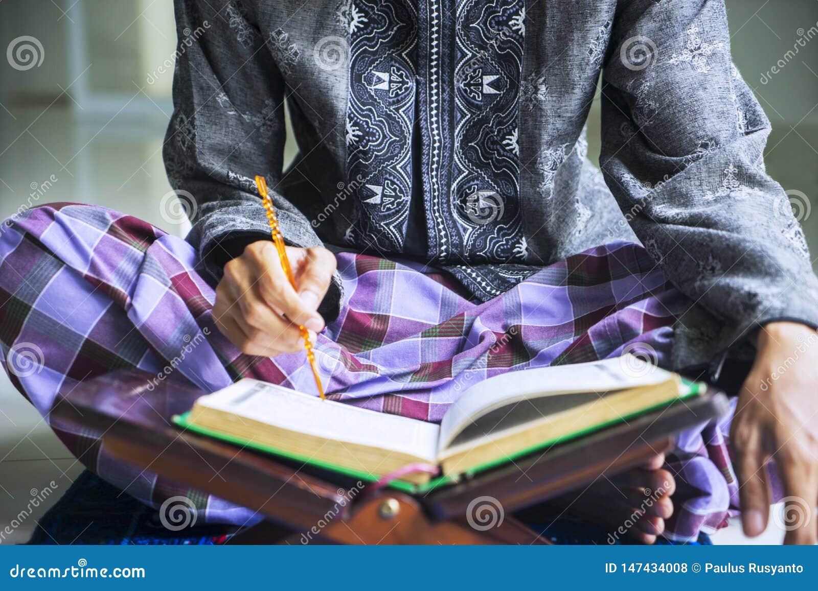 Jeune homme musulman avec un bâton et un Quran