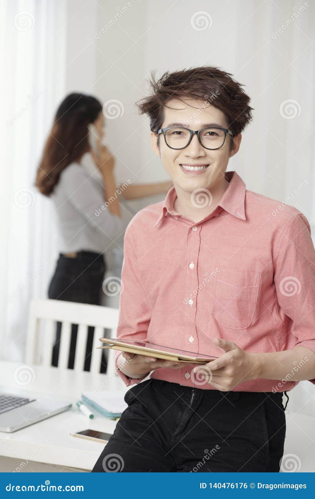 Jeune homme occasionnel avec le comprimé dans le bureau