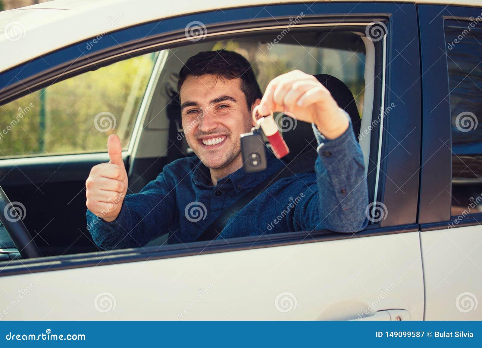 Jeune homme occasionnel portant des cl?s bleues de voiture de participation de chemise hors de la fen?tre, montrant le pouce vers