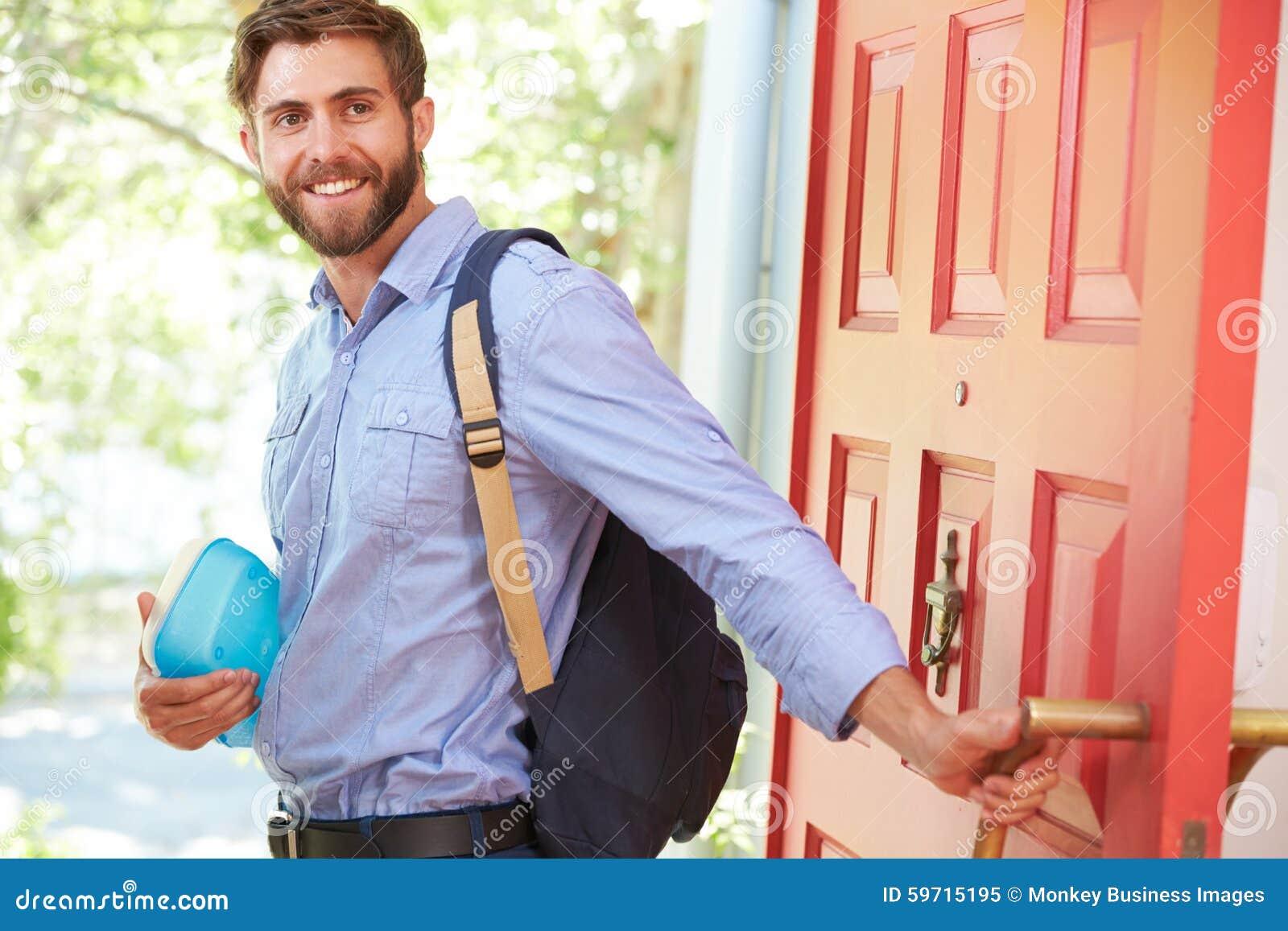 Jeune homme partant à la maison pour le travail avec le déjeuner emballé