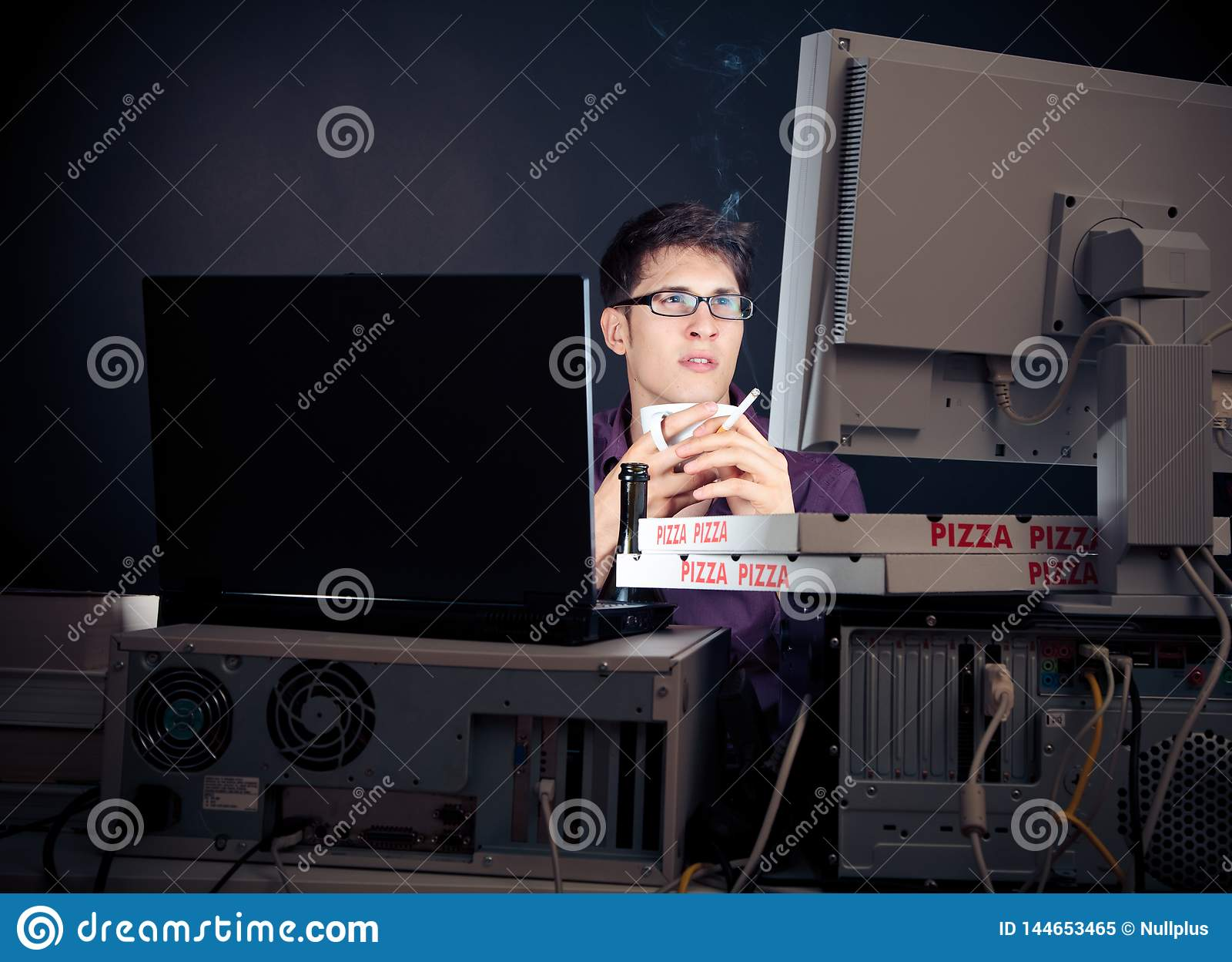 Jeune homme passant sa nuit avec des ordinateurs