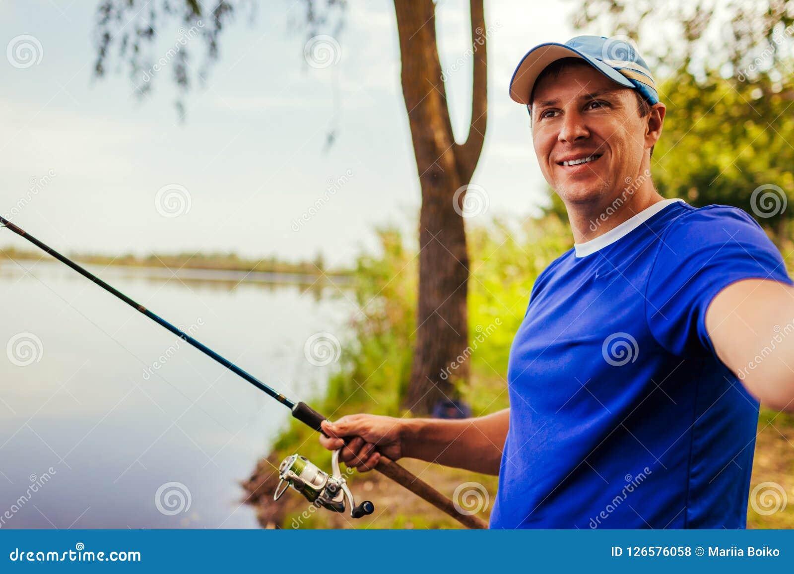 Jeune homme prenant le selfie tout en pêchant sur la rivière au coucher du soleil Fiserman heureux