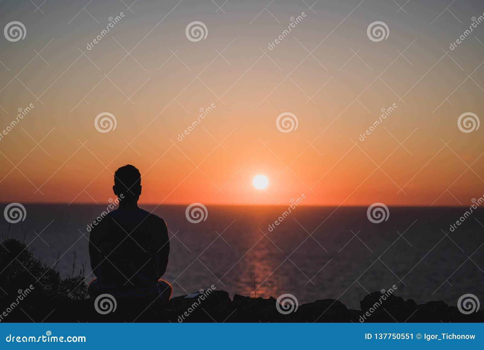 Jeune homme regardant au coucher du soleil au-dessus de la mer Concept appréciant et de détente, plein des expériences inoubliabl