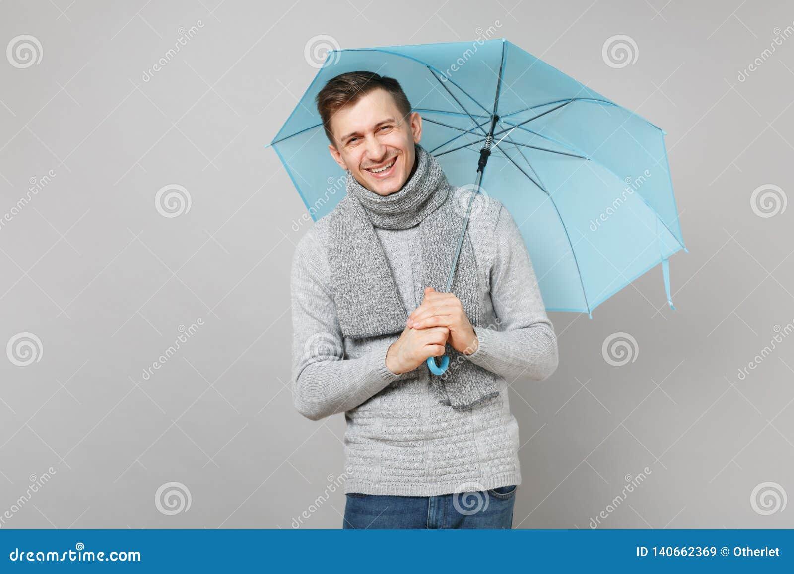 Jeune homme riant dans le chandail gris, écharpe jugeant le parapluie bleu d isolement sur le fond gris, portrait de studio Sain