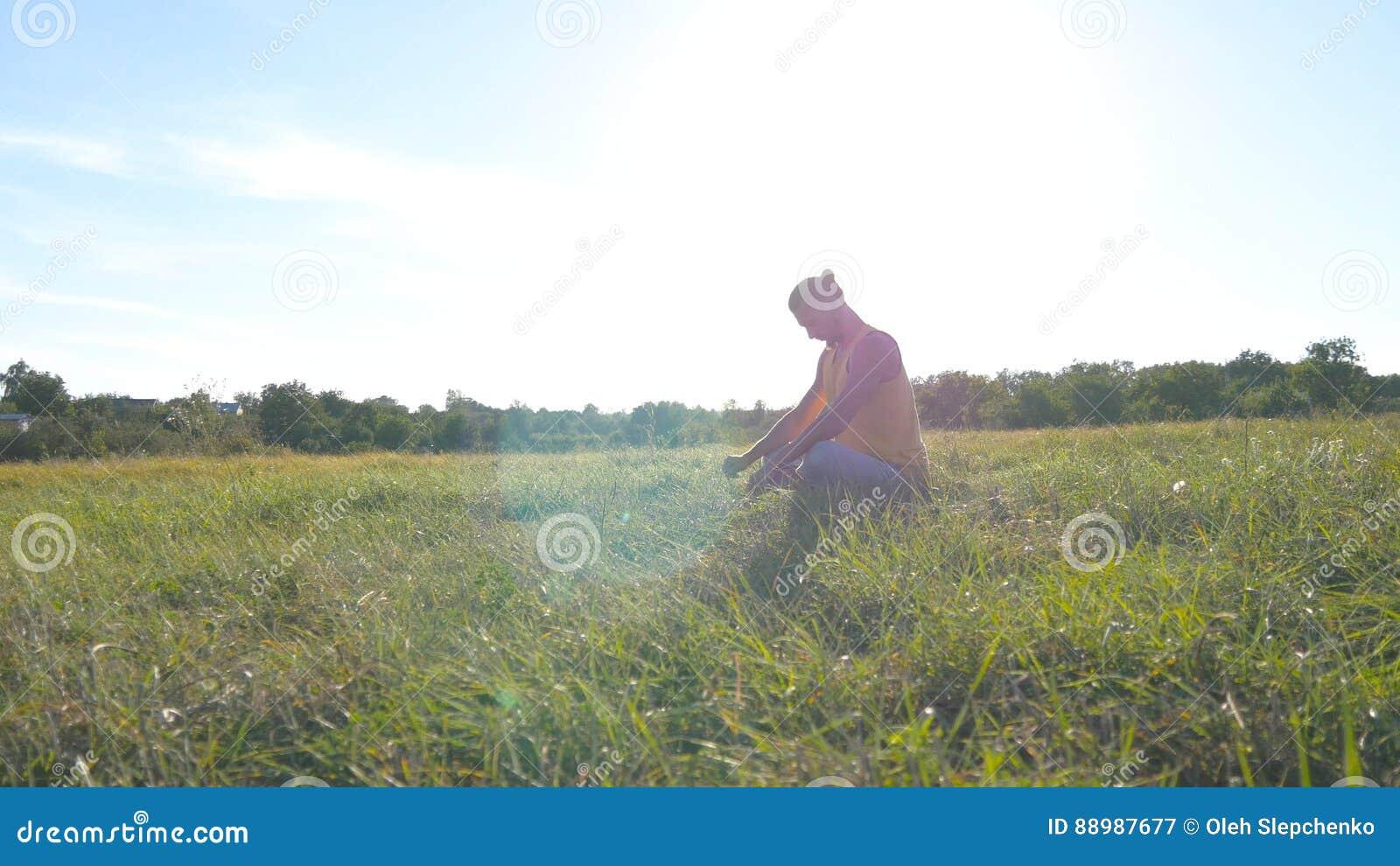 Jeune homme s asseyant à l herbe verte dans le pré et faisant l exercice de yoga Type musculaire étirant son corps à la nature