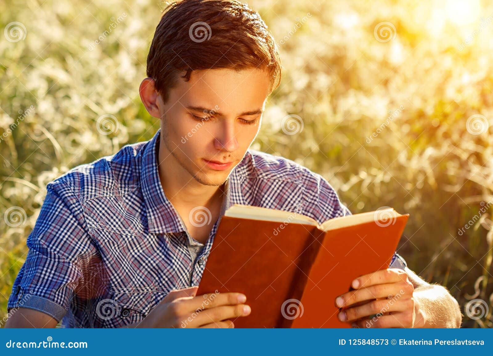 Jeune homme s asseyant en nature lisant un livre