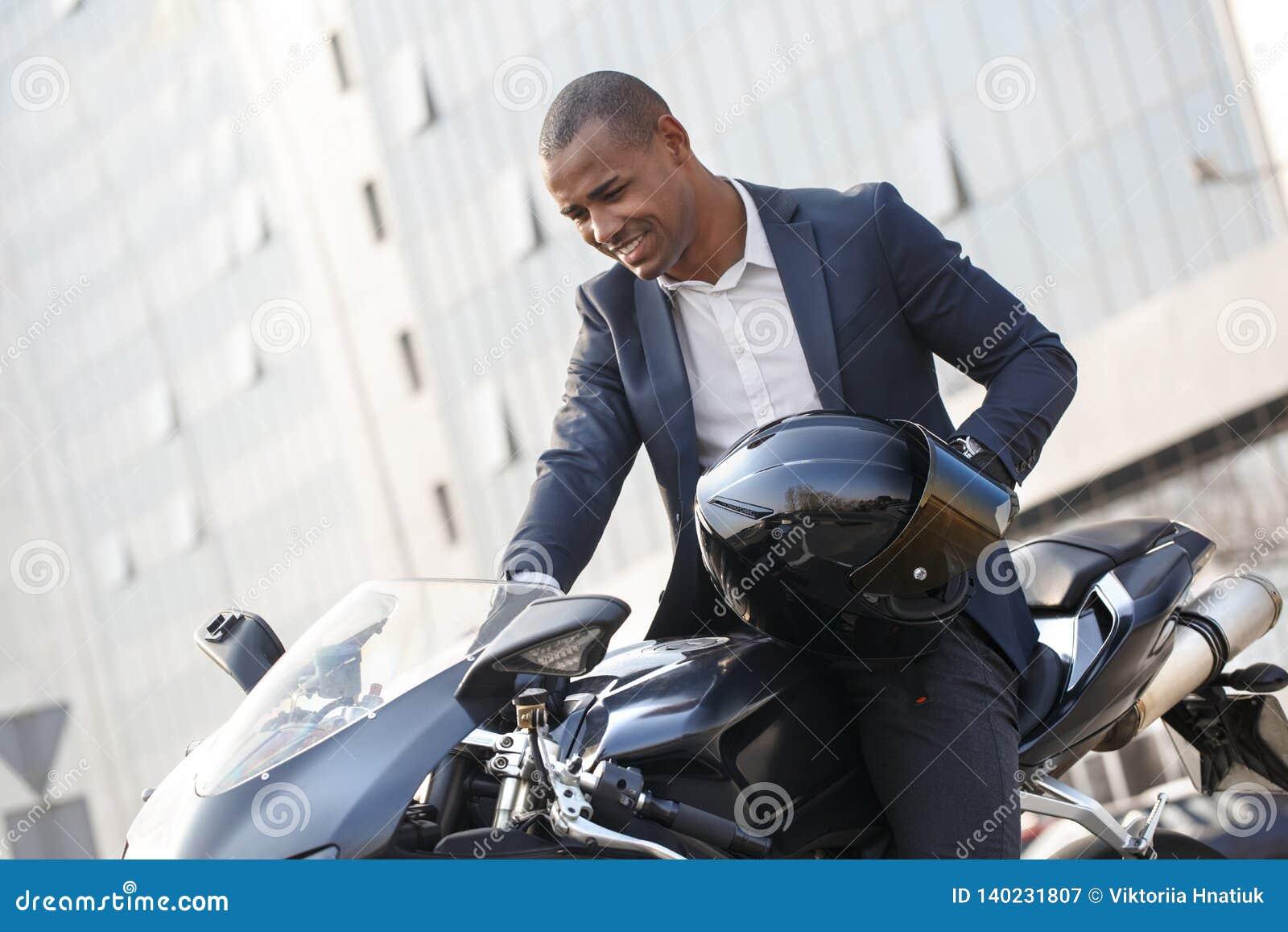 Jeune homme s asseyant sur la moto avec le casque mettant en marche le moteur excité