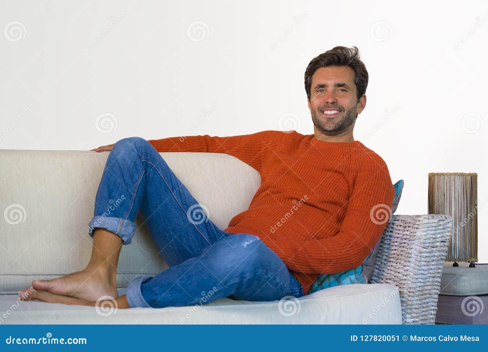 Jeune homme 30s attirant et heureux souriant séance décontractée et confortable au divan de sofa de salon dans son acclamation mo