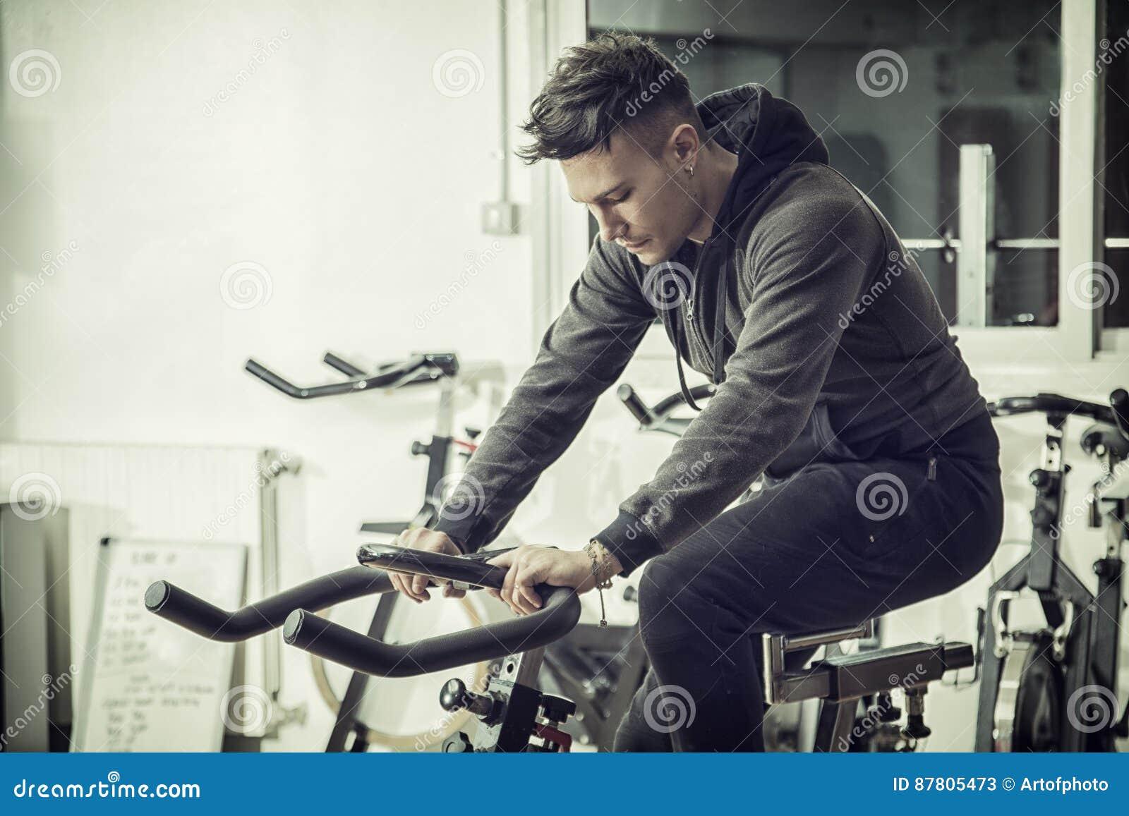 Jeune homme s exerçant dans le gymnase : rotation sur le vélo stationnaire