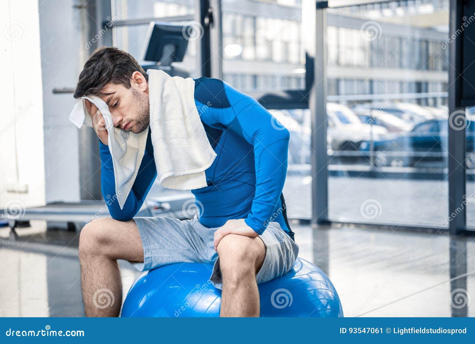 Jeune homme se reposant sur la boule de forme physique au gymnase
