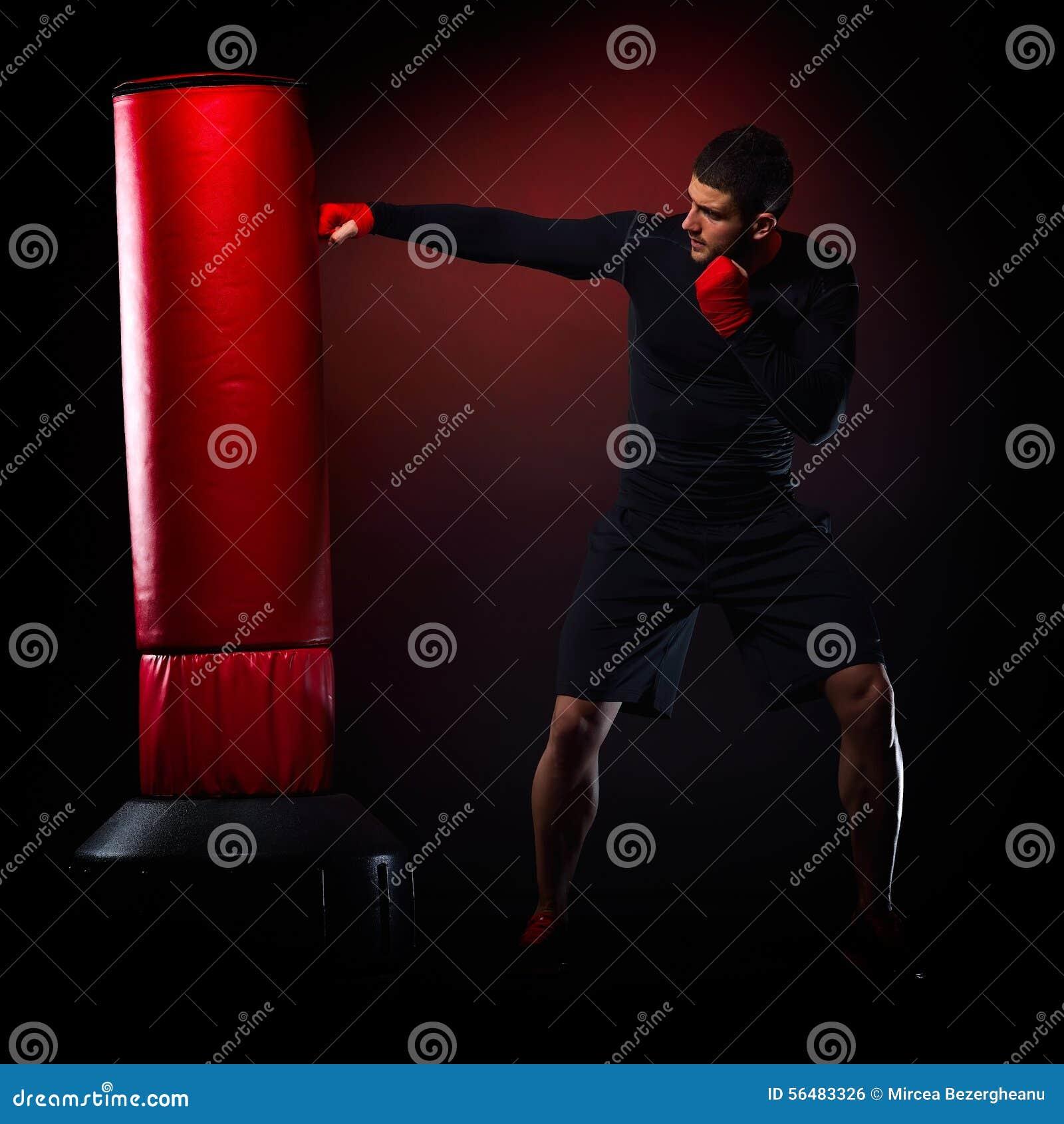 Jeune homme se tenant s exerçant avec le sac de boxe
