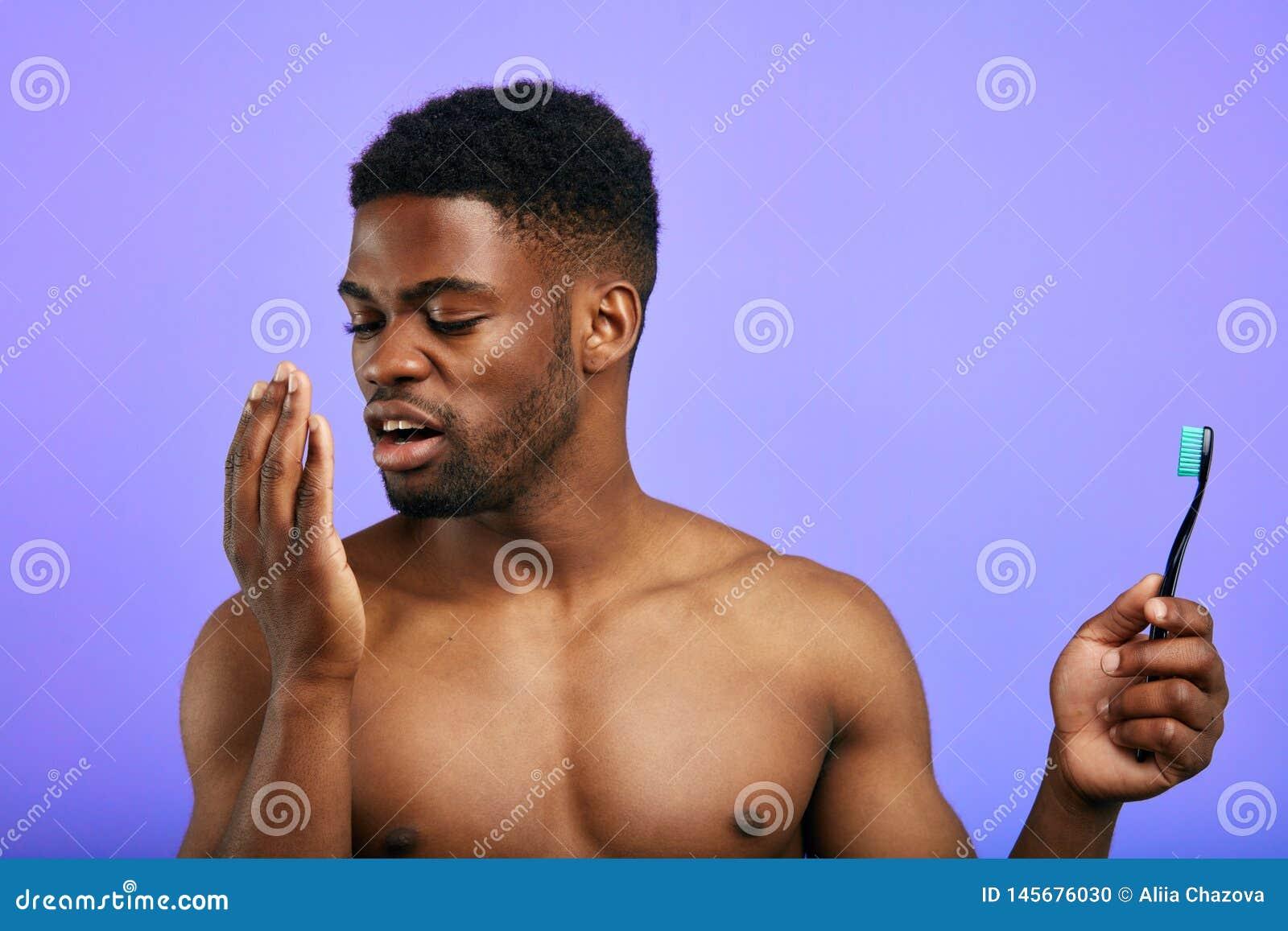 Jeune homme soufflant à la paume pour découvrir l odeur de sa bouche