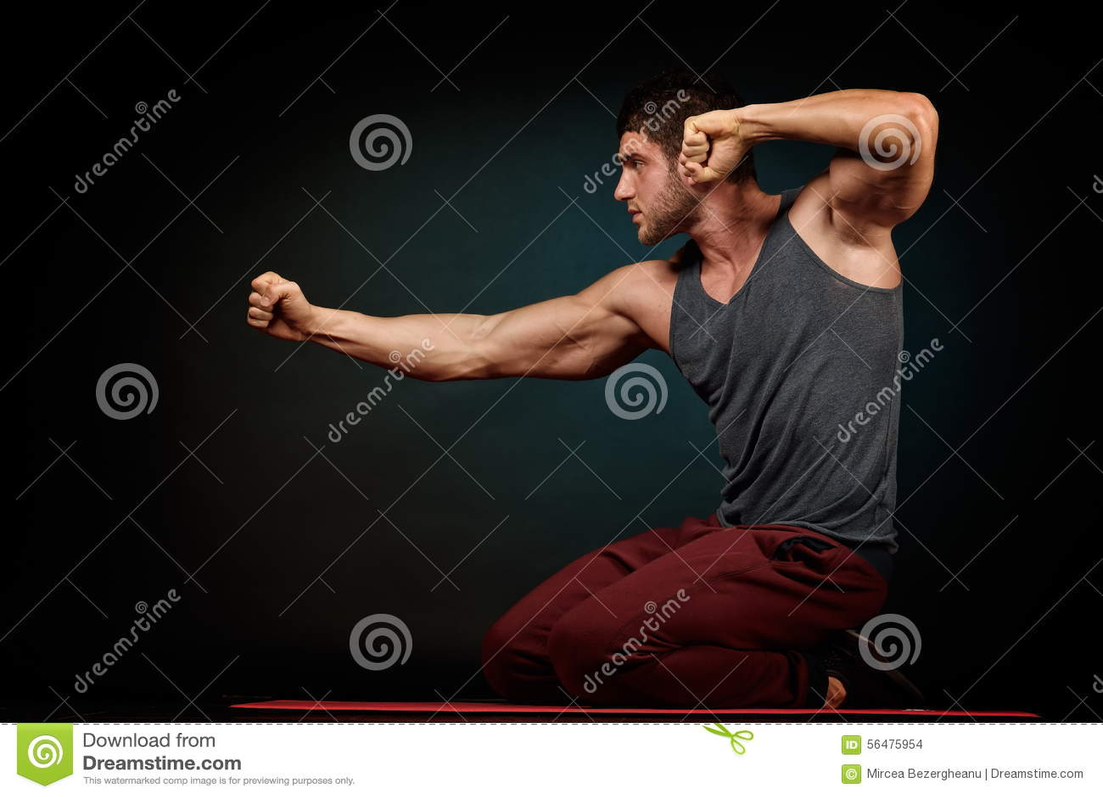 Jeune homme sportif dans le studio avec le fond foncé