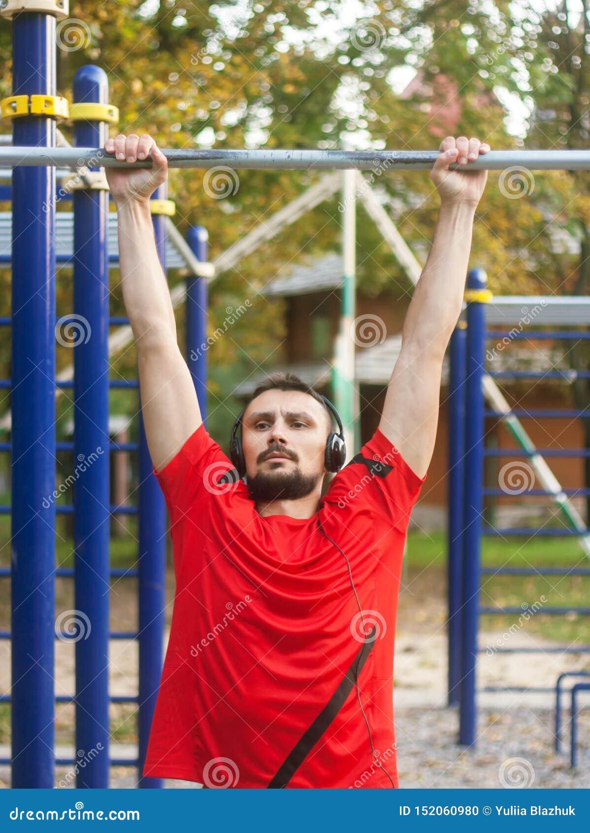 Jeune homme sportif faisant des exercices de sport dehors en parc