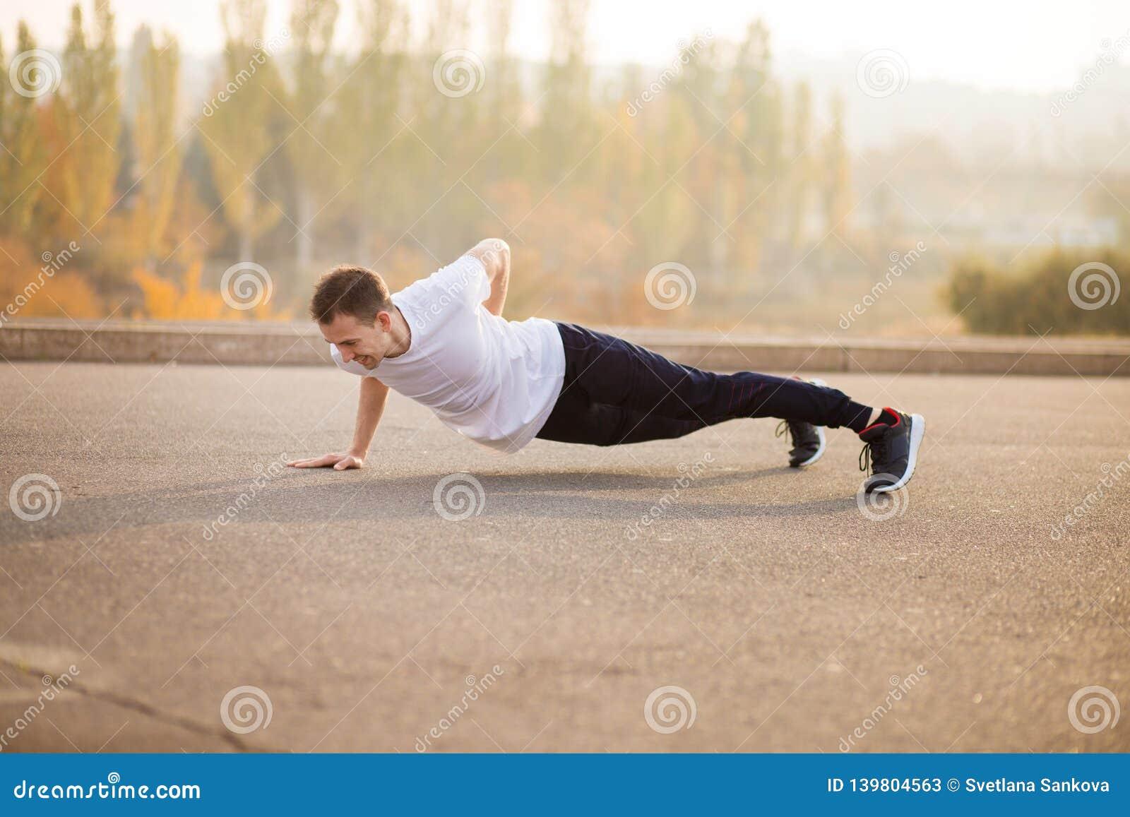 Jeune homme sportif faisant l extérieur de poussée  Homme sportif Le type s est engagé dans les sports sur la nature