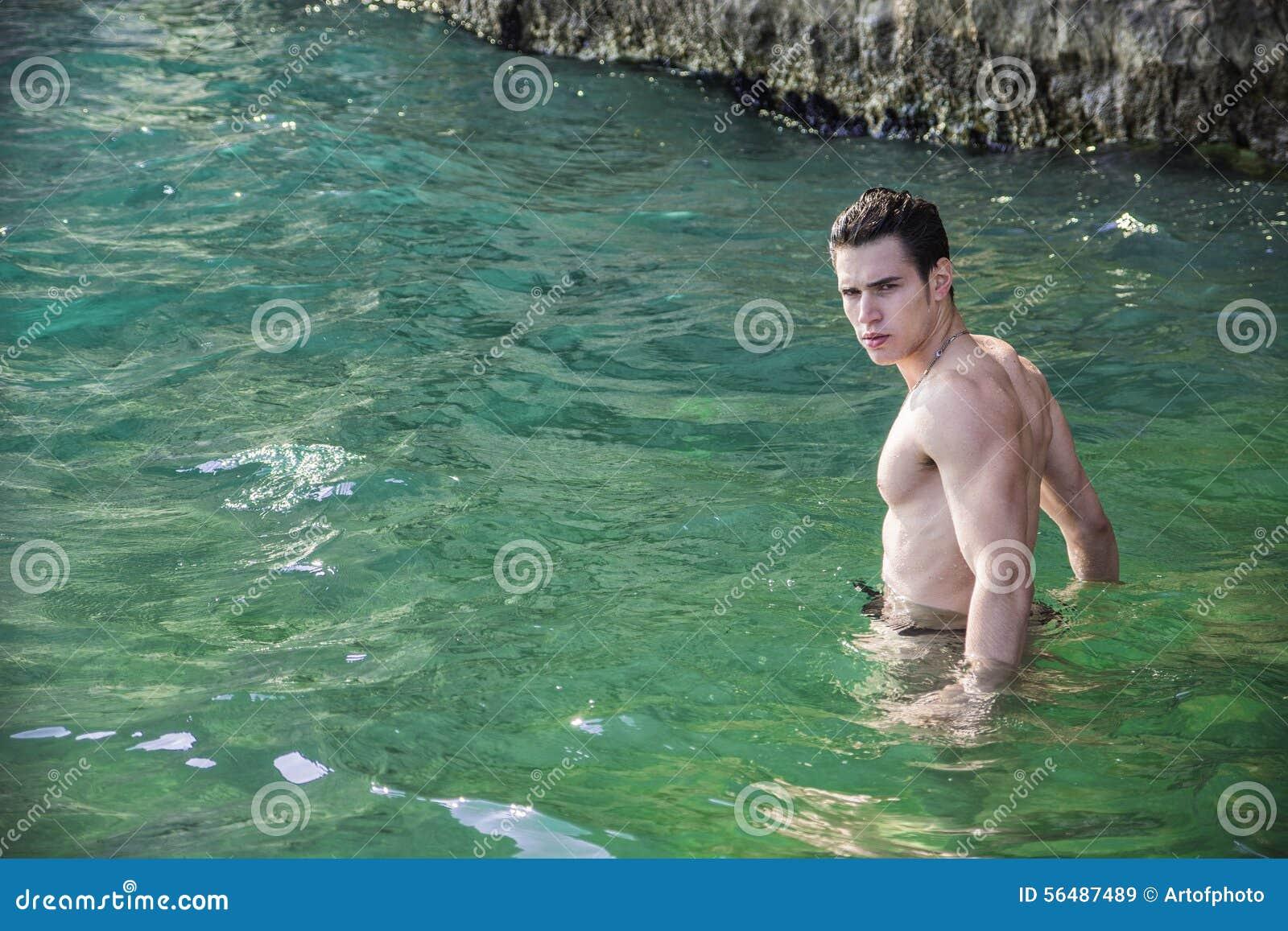 Jeune homme sportif sans chemise se tenant dans l eau par