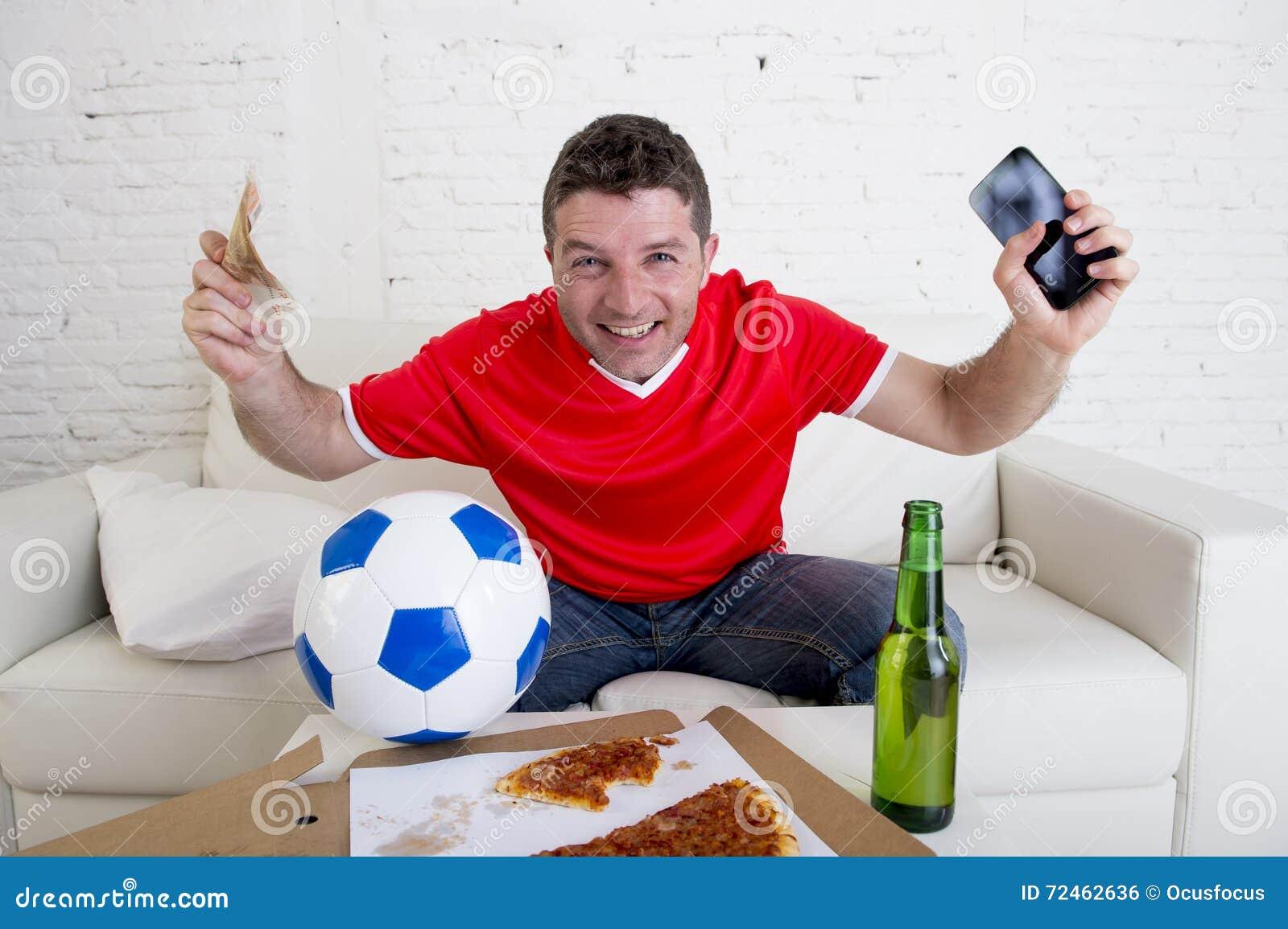 Jeune homme tenant le téléphone portable et l argent dans des ses mains observant le jeu de fottball sur le concept de jeu d Inte