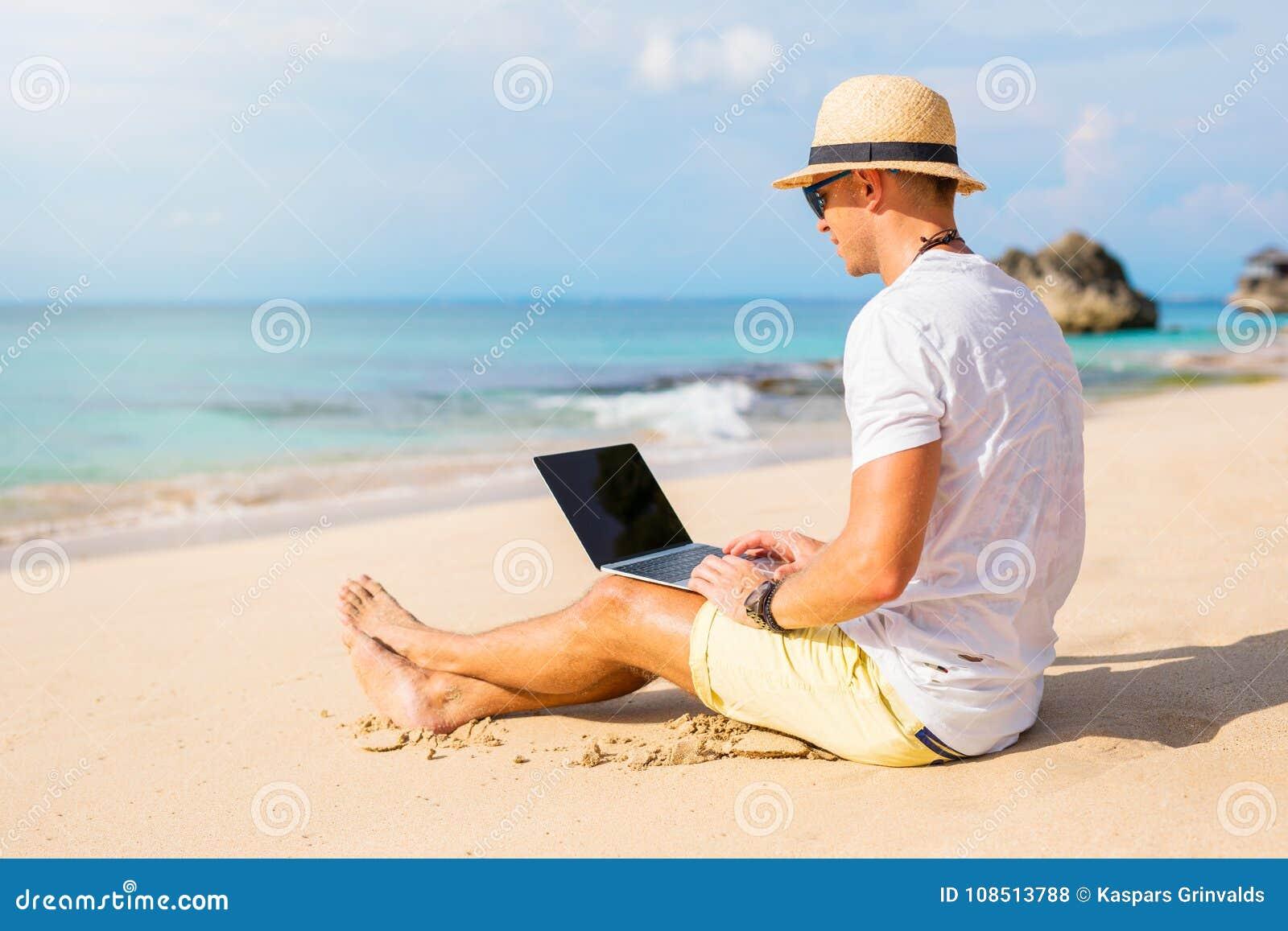 Jeune homme travaillant avec l ordinateur portable sur la plage