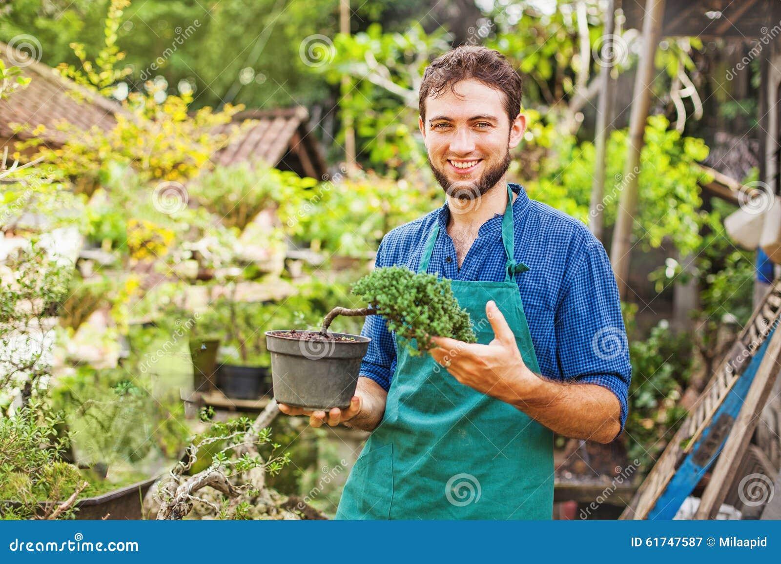 Jeune jardinier avec des bonsaïs