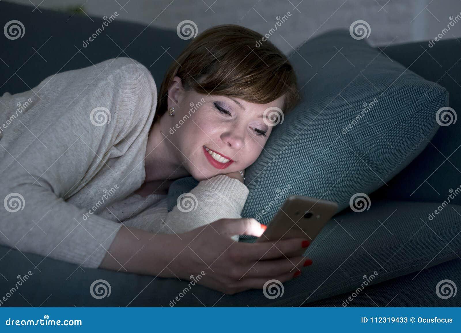 Jeune jolie et heureuse femme rouge de cheveux sur son 20s ou 30s se trouvant sur le divan à la maison ou lit utilisant le téléph