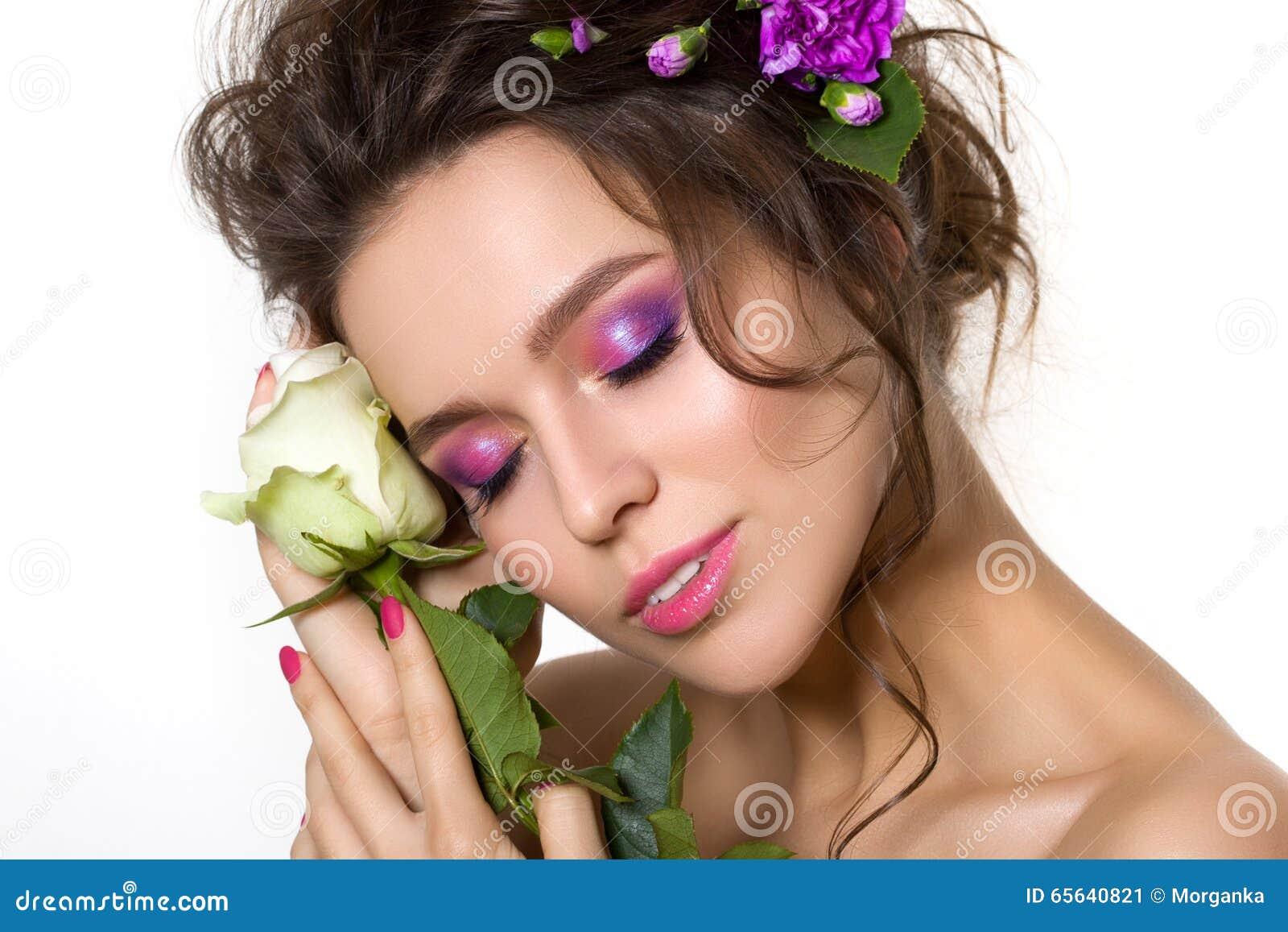 Jeune jolie femme avec le maquillage rose lumineux