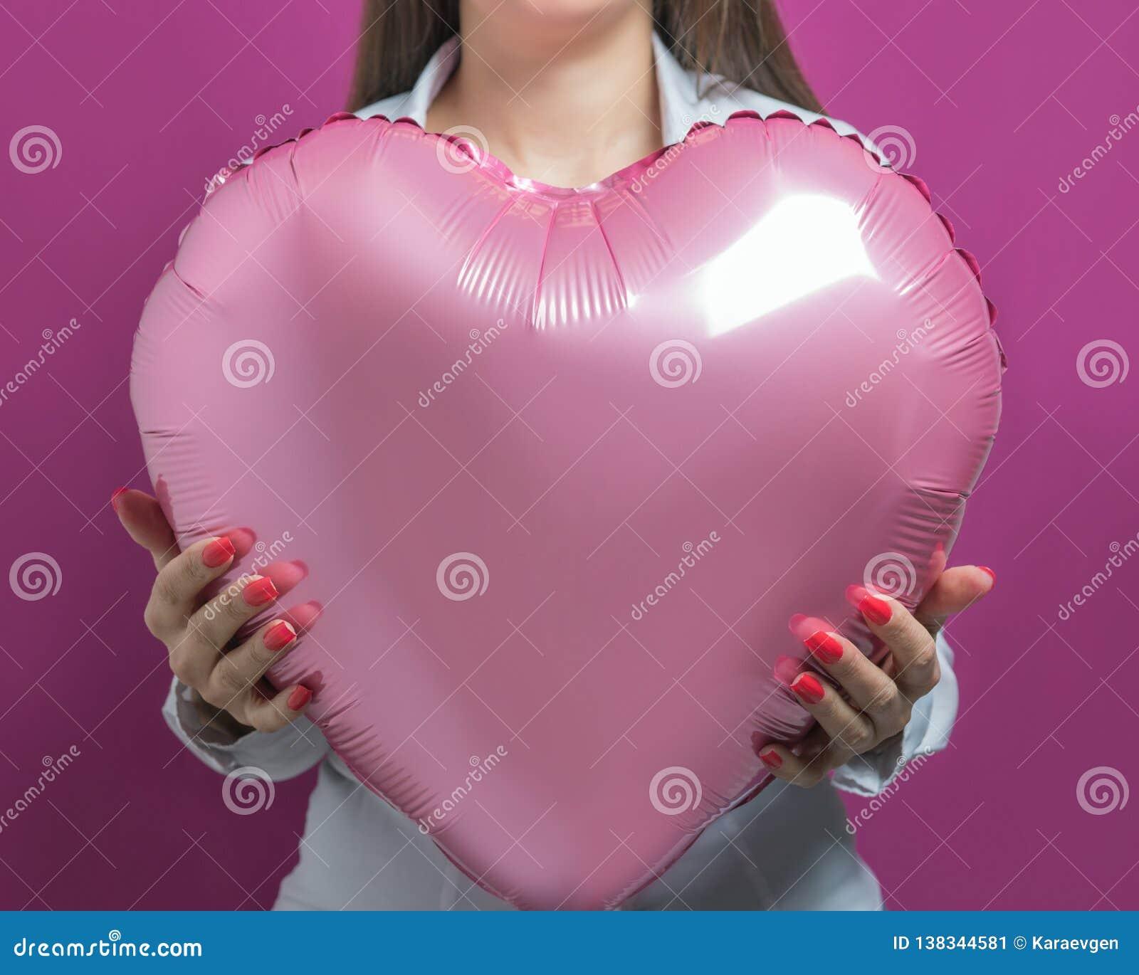 Jeune jolie femme tenant un ballon à air en forme de coeur Concept de jour du ` s de Valentine