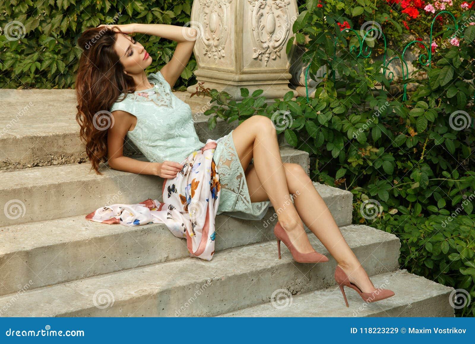 Jeune la dame élégante, exquise et élégante pose sur des escaliers du beau domaine