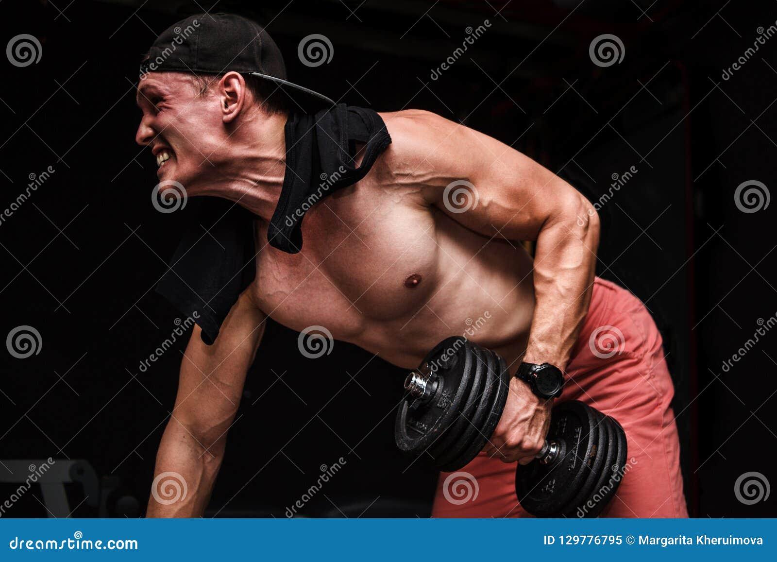 Jeune mâle adulte beau faisant des rangées d haltère d un-bras sur le banc dans le gymnase