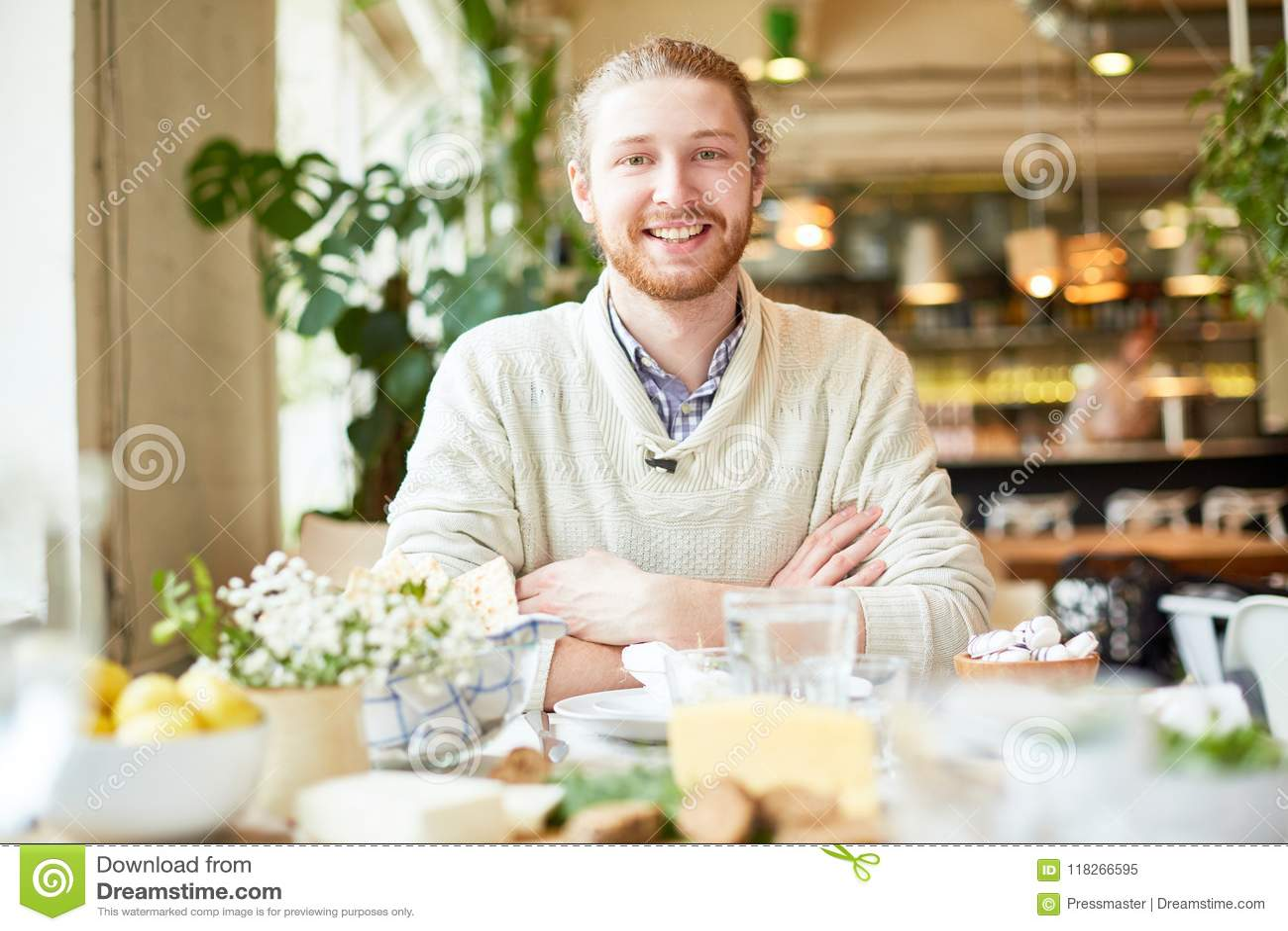 Jeune mâle souriant et regardant l appareil-photo en café