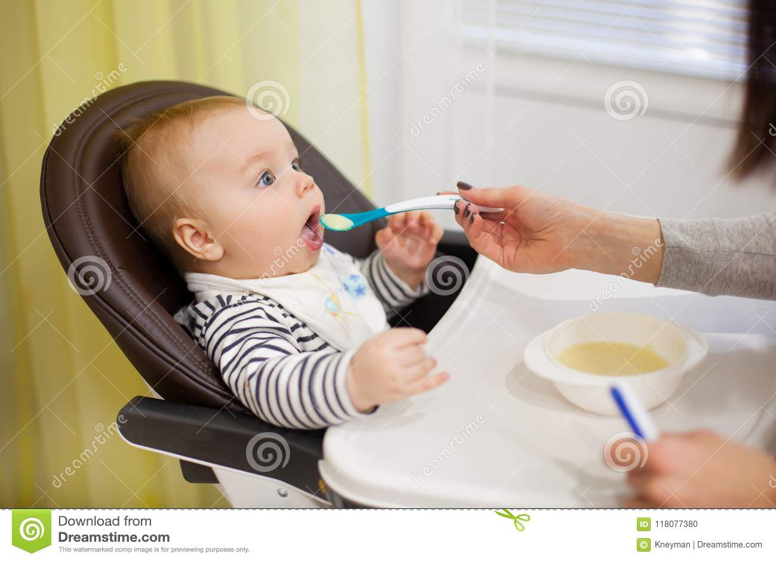 Jeune mère alimentant son petit fils de bébé avec le gruau, qui se reposant dans la haute chaise de bébé pour l alimentation