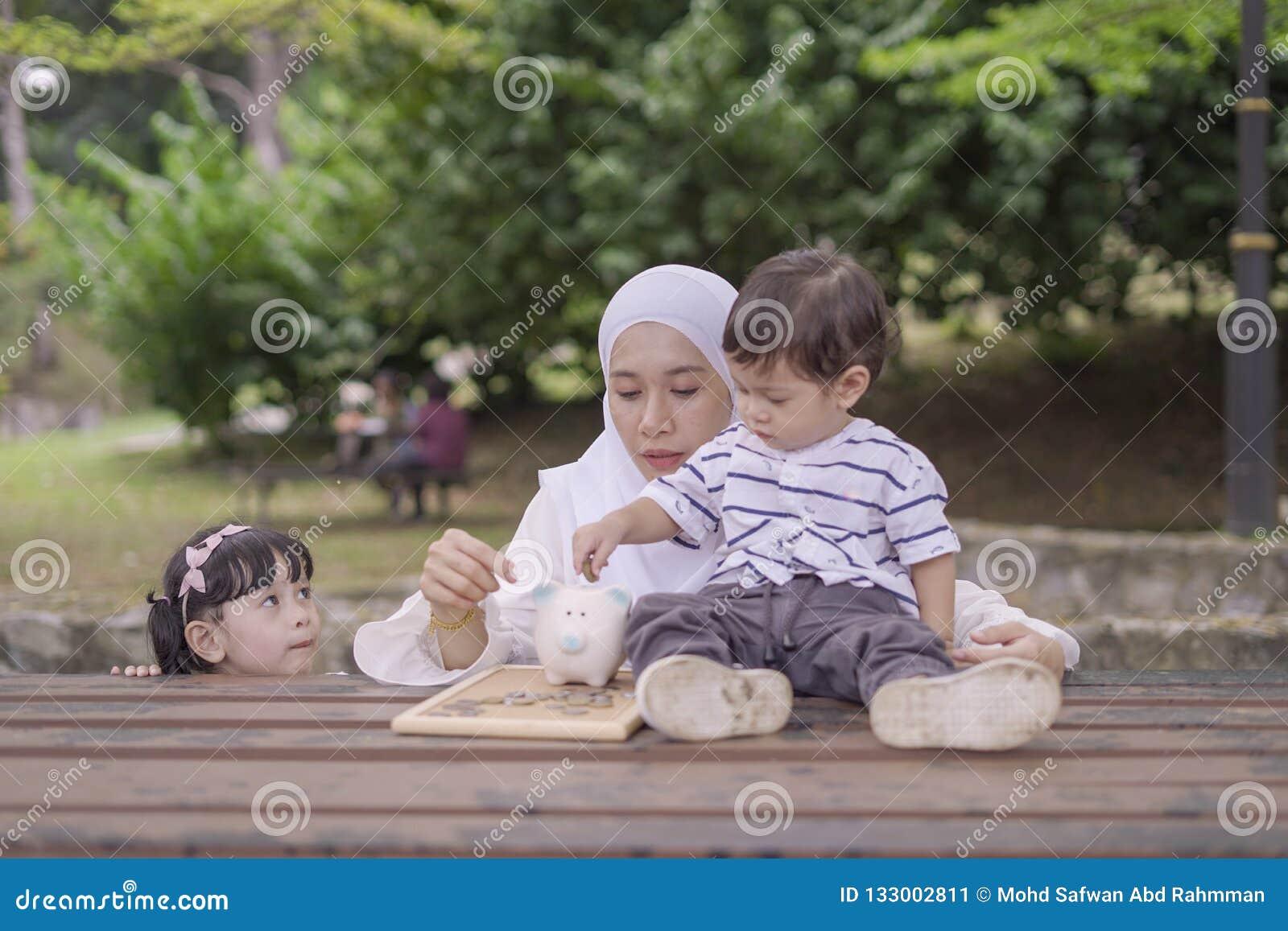 Jeune mère asiatique enseigner ses enfants à l argent économisant dans la tirelire pour un meilleur avenir