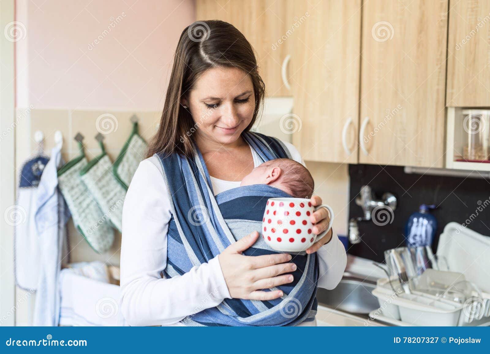 Jeune mère dans la cuisine avec son fils dans la bride