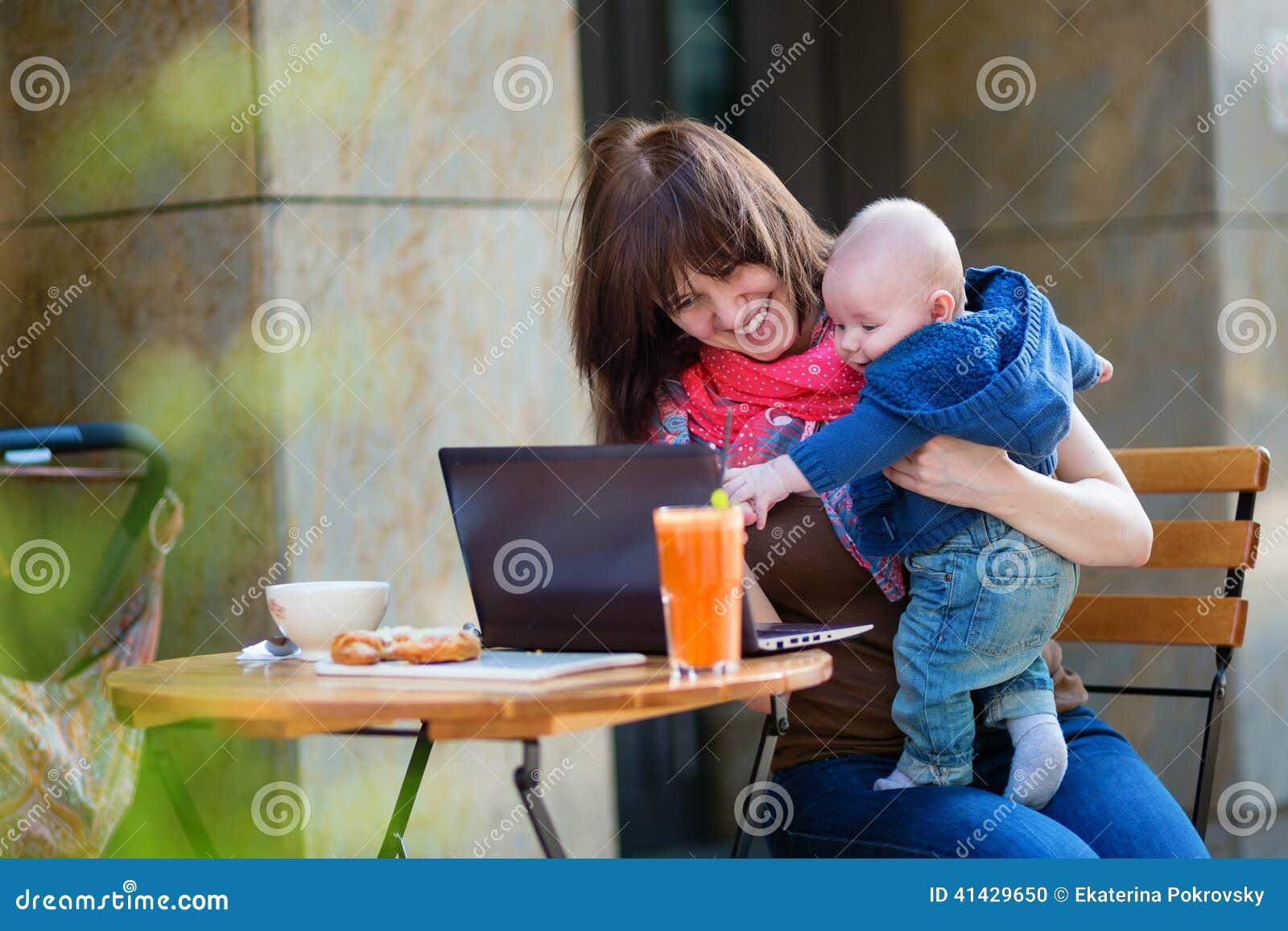 Jeune mère de fonctionnement avec le petit fils dans un café