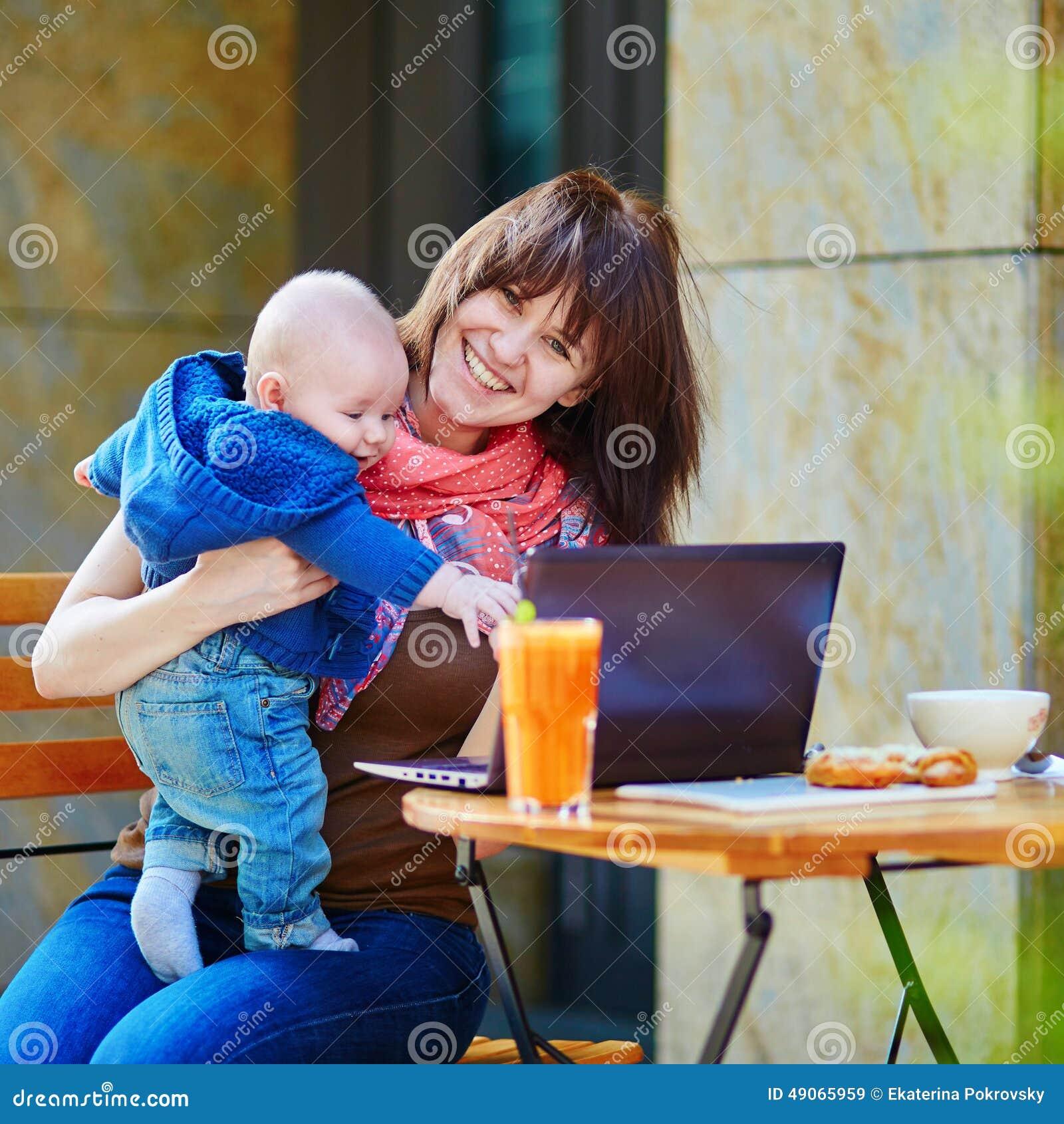 Jeune mère de fonctionnement avec son fils dans un café